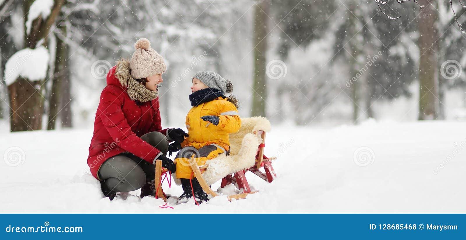 Mutter-/Kindermädchengespräch mit kleinem Kind während des Rodelns im Winterpark