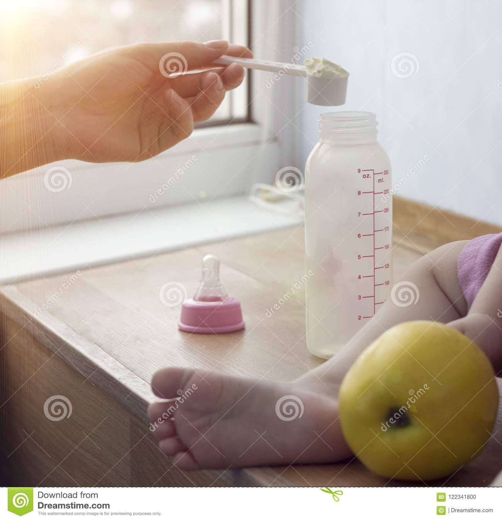 Mutter kocht Säuglingsnahrung für das Kind, einen Abschluss oben, eine Hand und eine kleine Flasche
