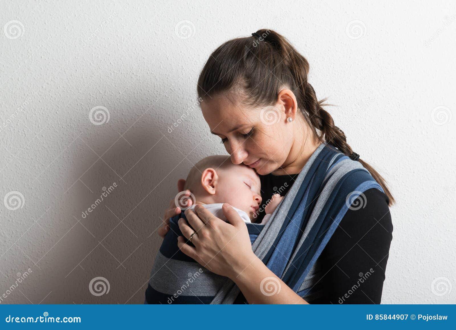 Mutter mit ihrem Babysohn, der im Riemen schläft Schönes Tanzen der jungen Frau der Paare