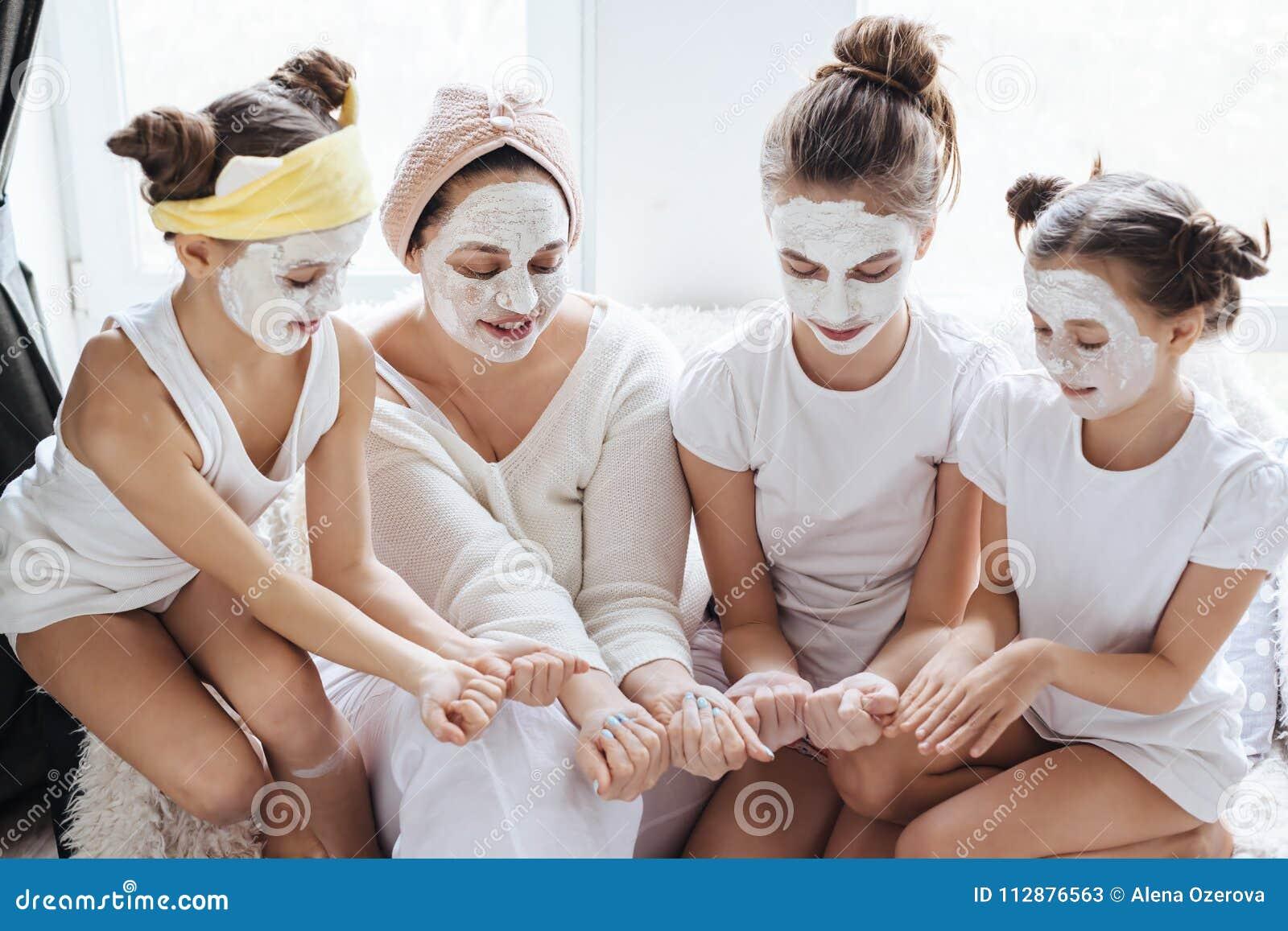 Mutter mit ihren Töchtern, die LehmGesichtsmaske machen