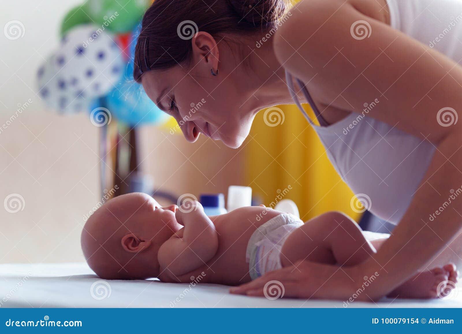 Mutter mit nettem Lächeln kümmert sich um ihrem neugeborenen Jungen auf ändernder Tabelle des Babys
