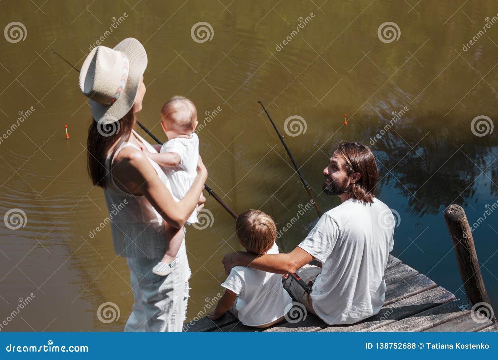 Mutter mit weniger Tochter auf ihren Händen schaut wie Vater- und Sohnfischen Alle Familie gekleidet in der weißen Kleidung