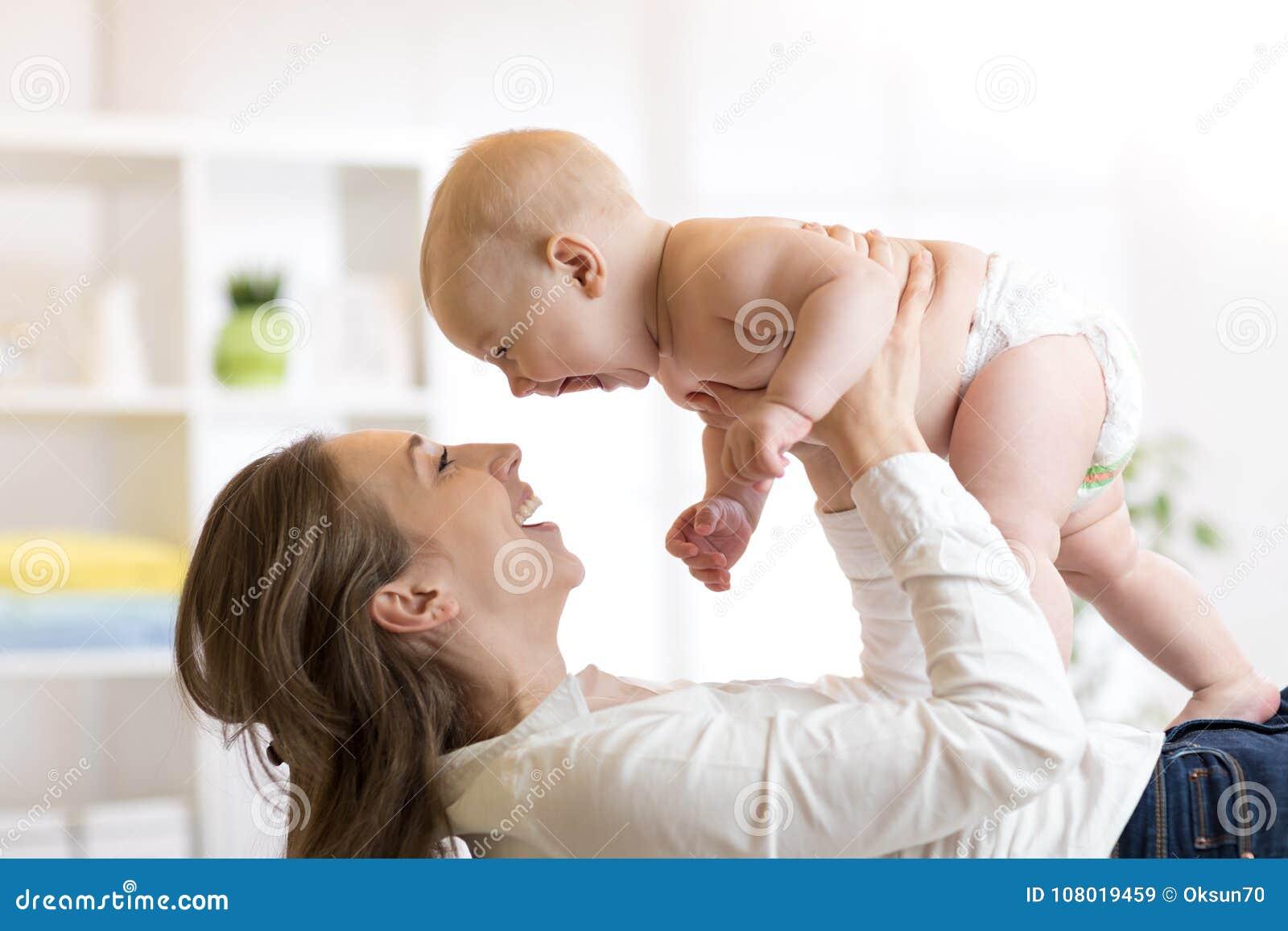 Mutter und Baby in der Windel, die im sonnigen Raum spielt Elternteil und Kleinkind, die sich zu Hause entspannen Familie, die Sp
