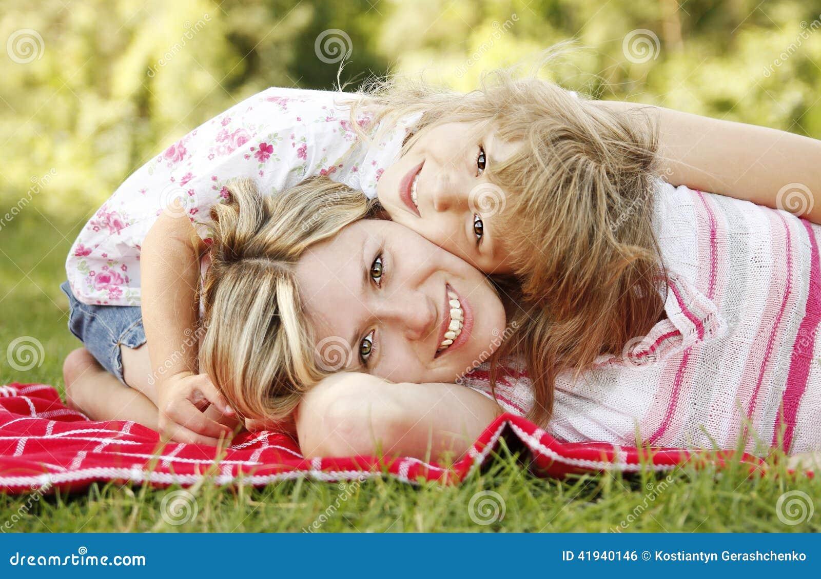 Mutter und ihre kleine Tochter liegen auf dem Gras