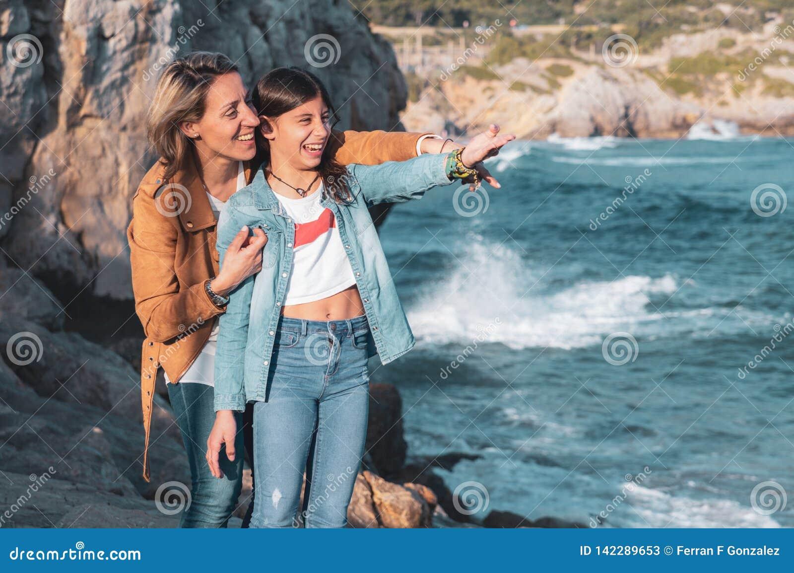 Mutter und jugendliche Tochter, die auf etwas im Mittelmeer lachen und zeigen