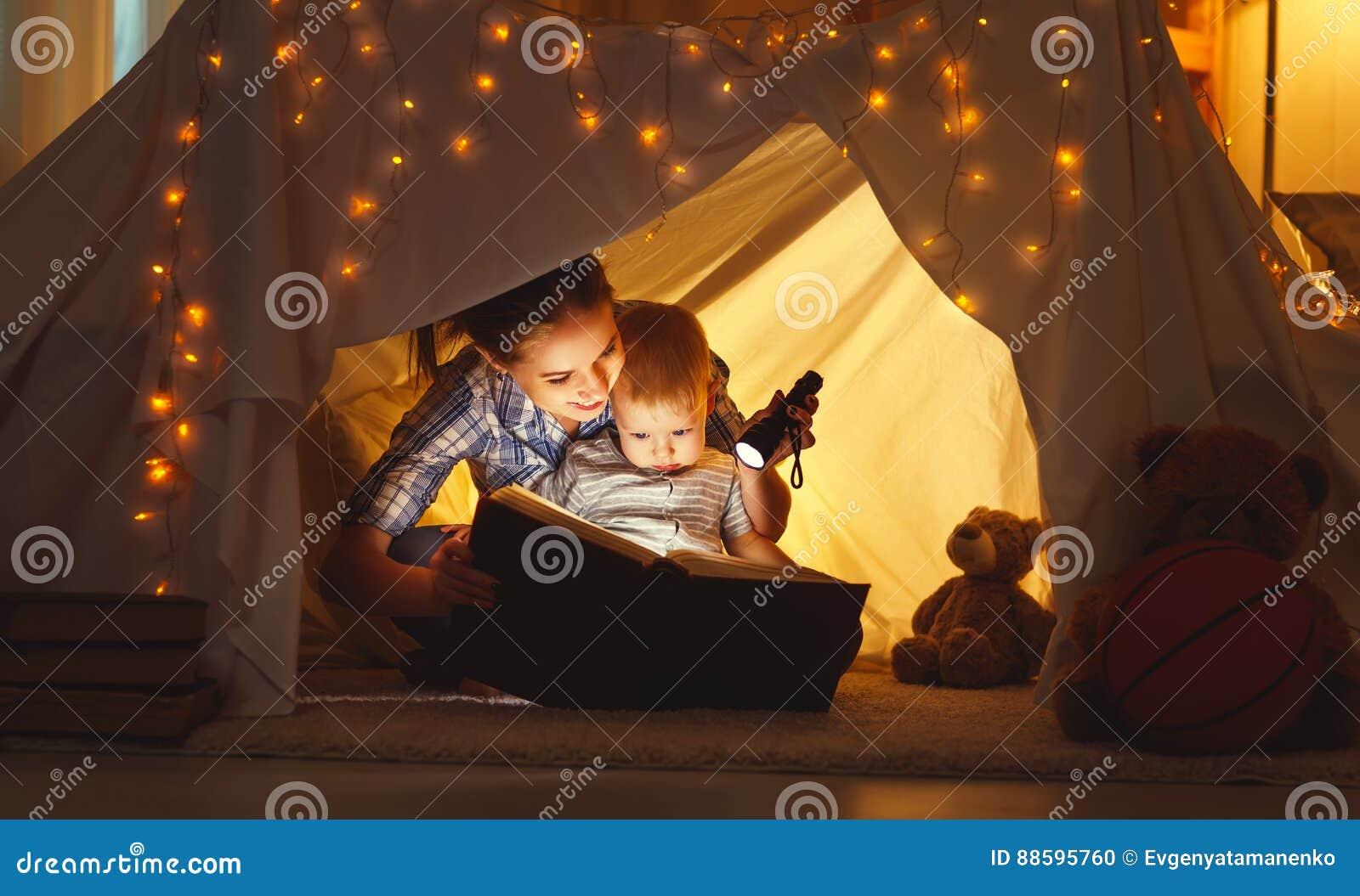 Mutter- und Kindertochter mit einem Buch und einer Taschenlampe vor gehen