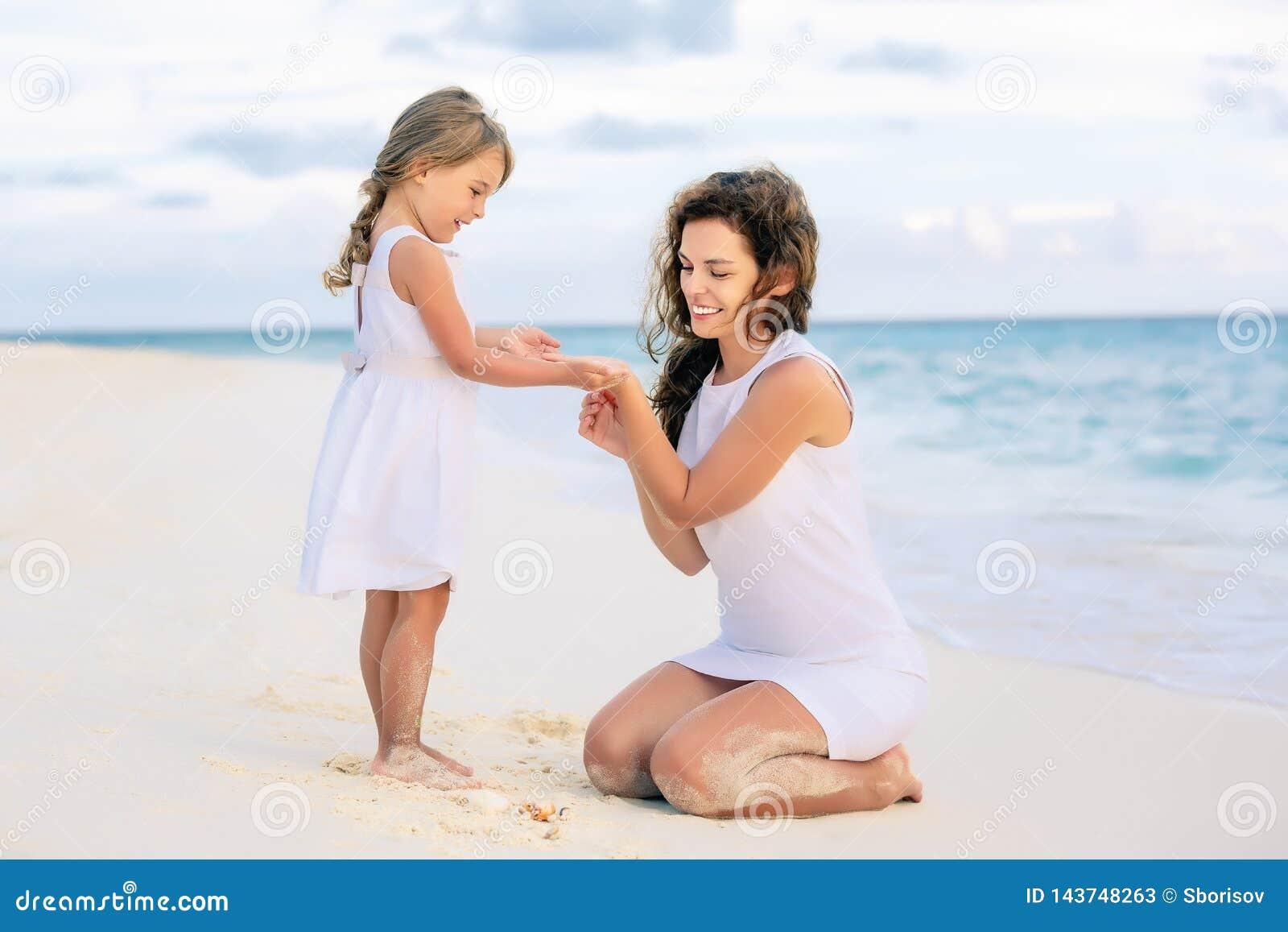 Mutter und kleine Tochter, die auf dem Strand auf Malediven an den Sommerferien spielen