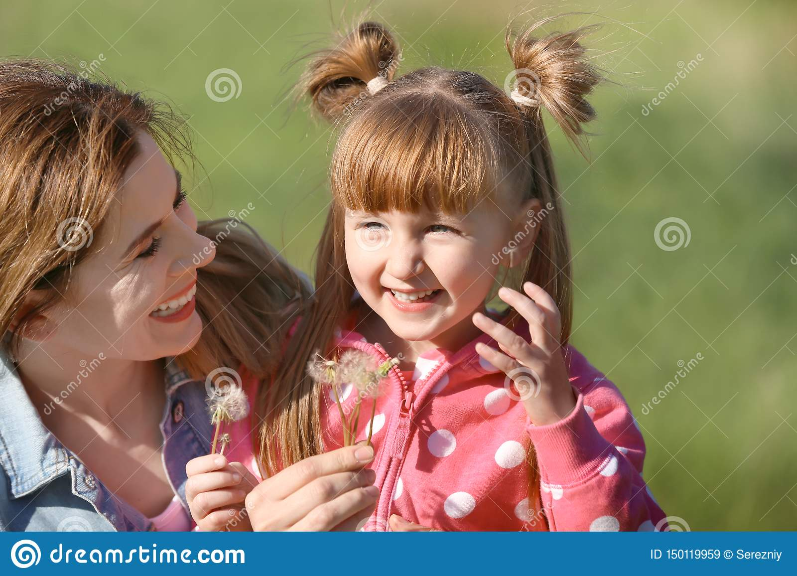 Mutter und kleine Tochter mit Löwenzahn im Park