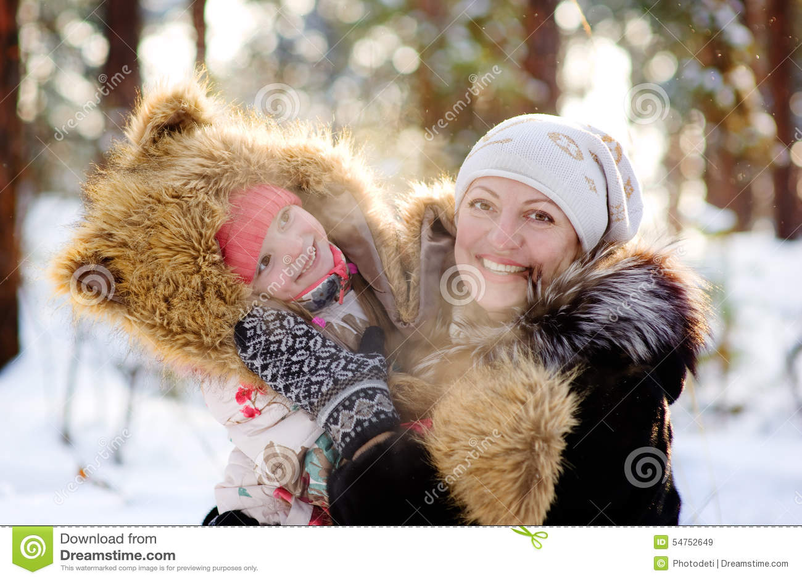 Mutter und kleines Mädchen, die im Winterwald lachen