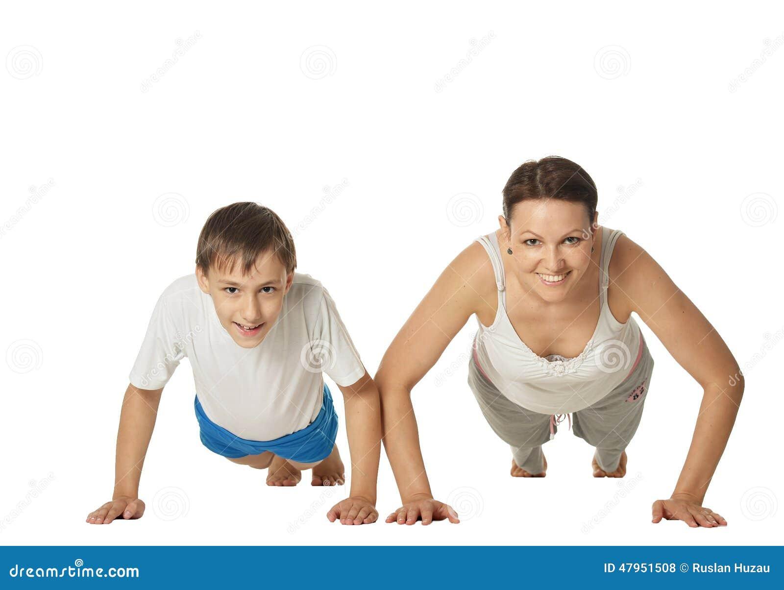 Junge Mutter und Sohn, welche die Übungen, lokalisiert auf weißem