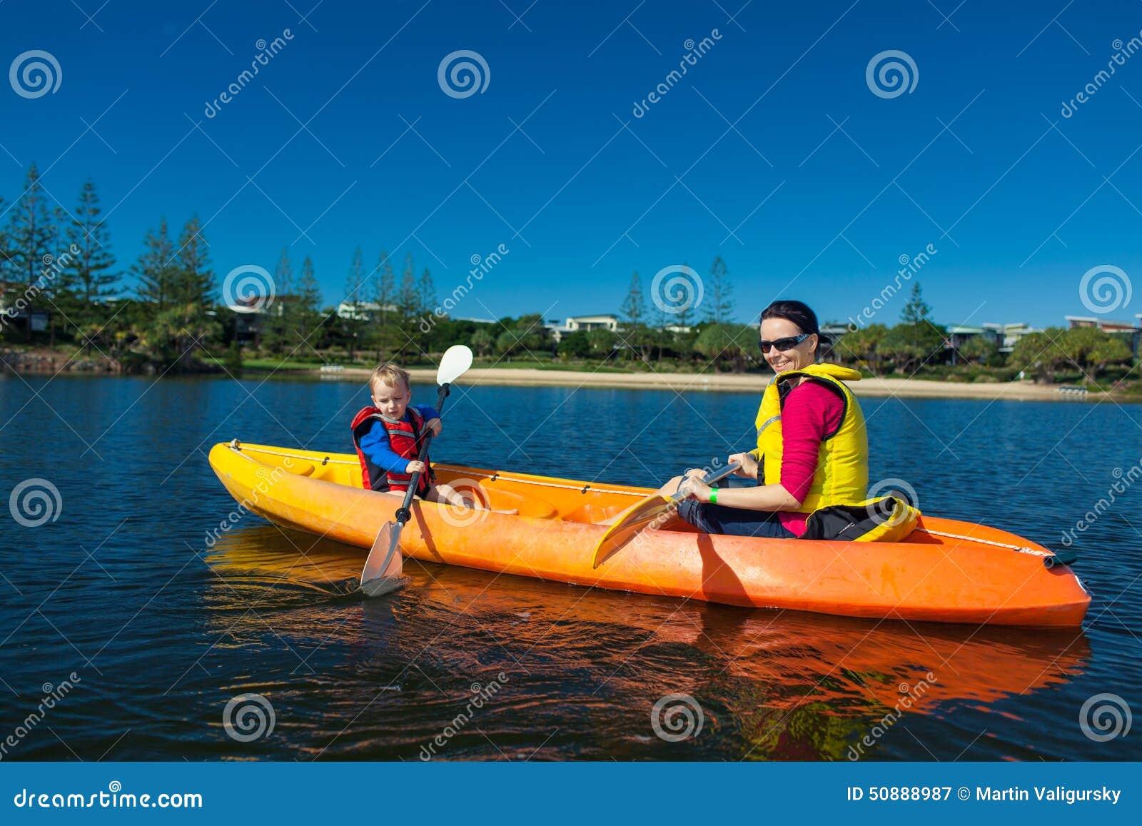 Mutter und Sohn, die in einem kleinen See Kayak fahren