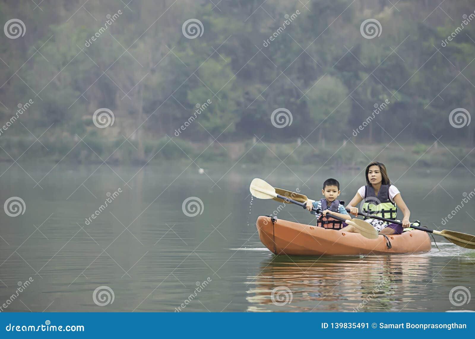 Mutter und Sohn, die im Reservoir Kayak fahren