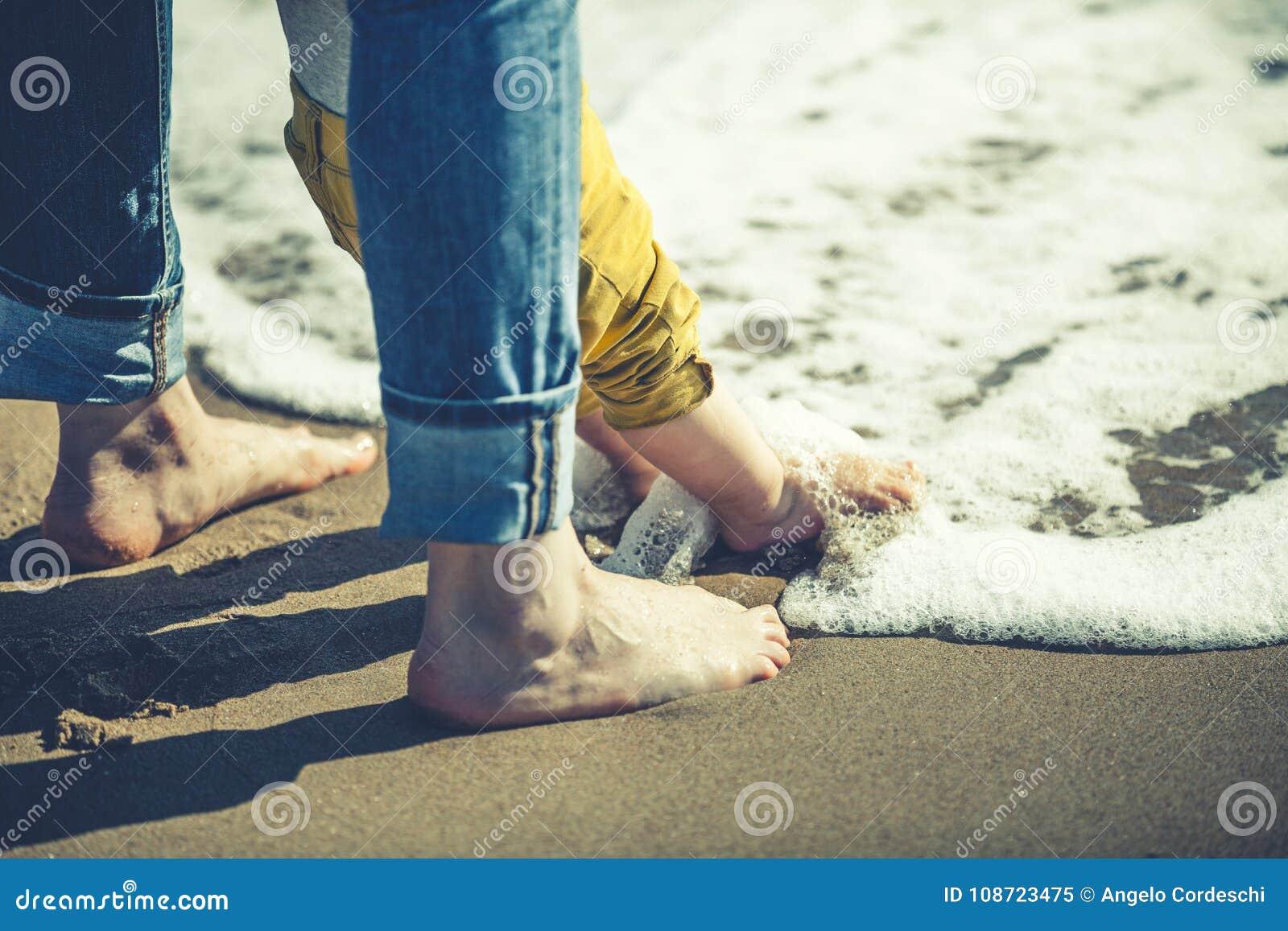 Mutter und Sohn mit Füßen im Ufer wässern Liebe und Schutz