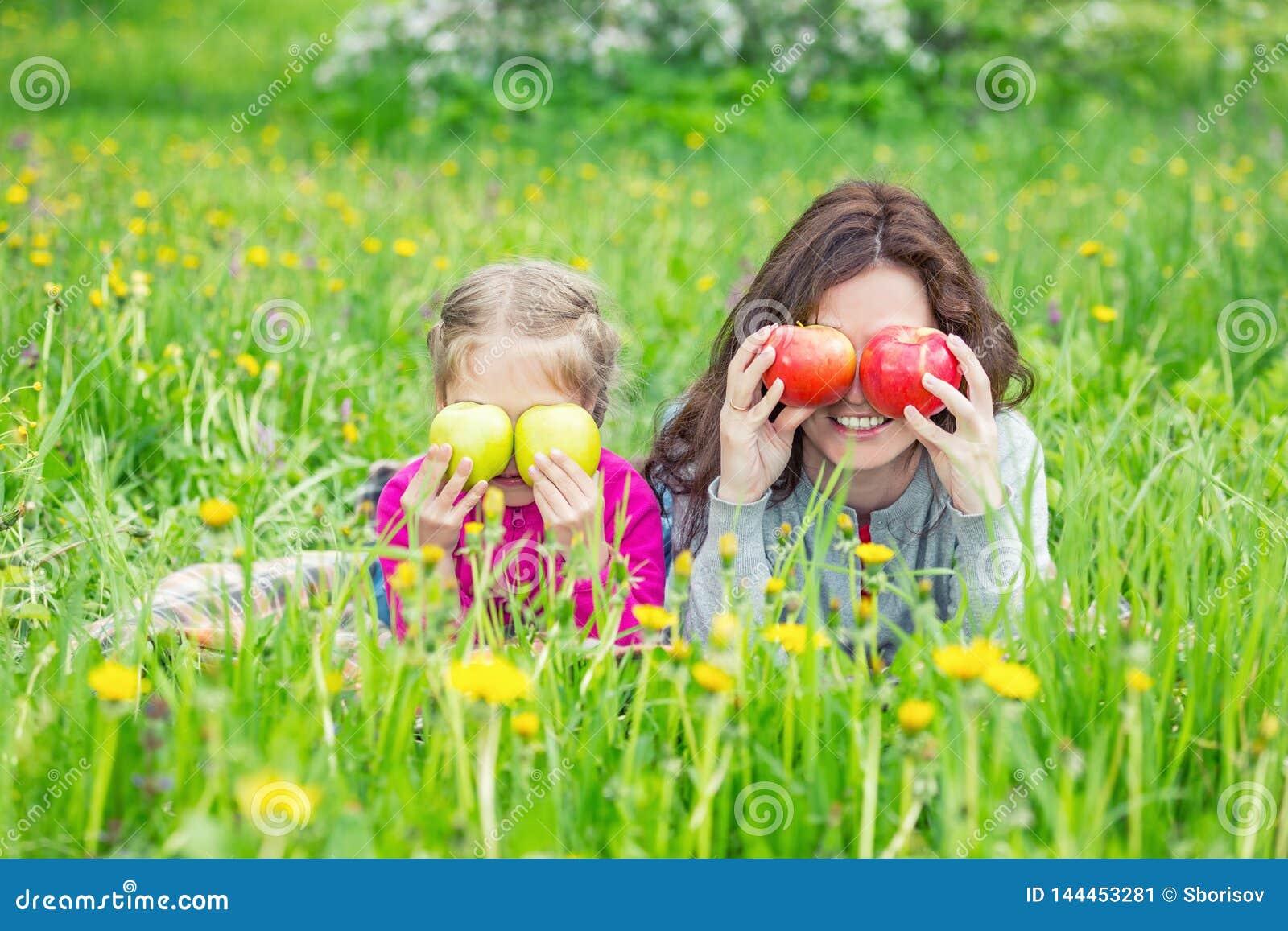 Mutter und Tochter auf sonniger Wiese mit Äpfeln in den Händen