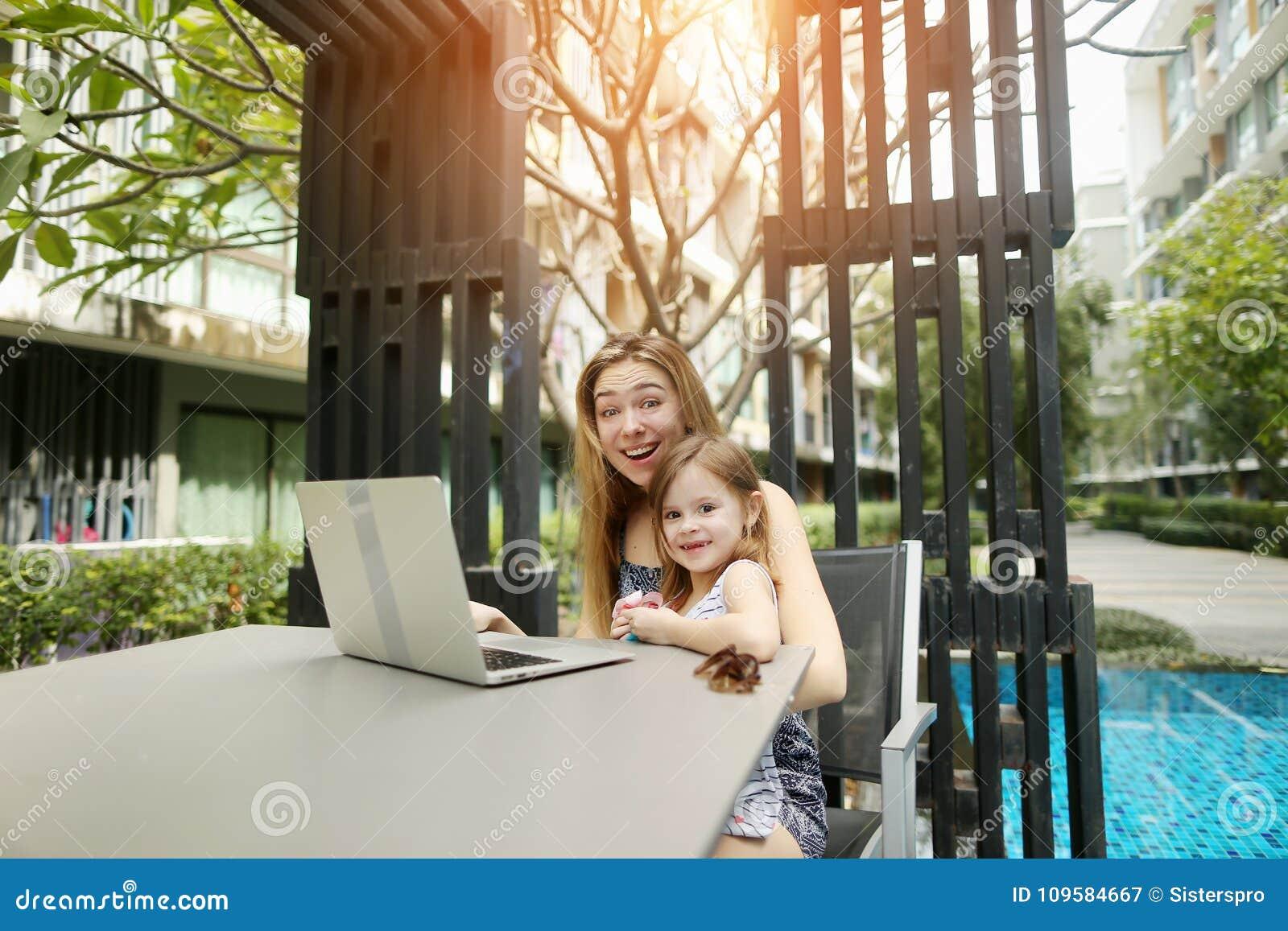 Mutter und Tochter benutzen Laptop für das on-line-Einkaufen auf Hintergrund des Swimmingpools am sonnigen Tag