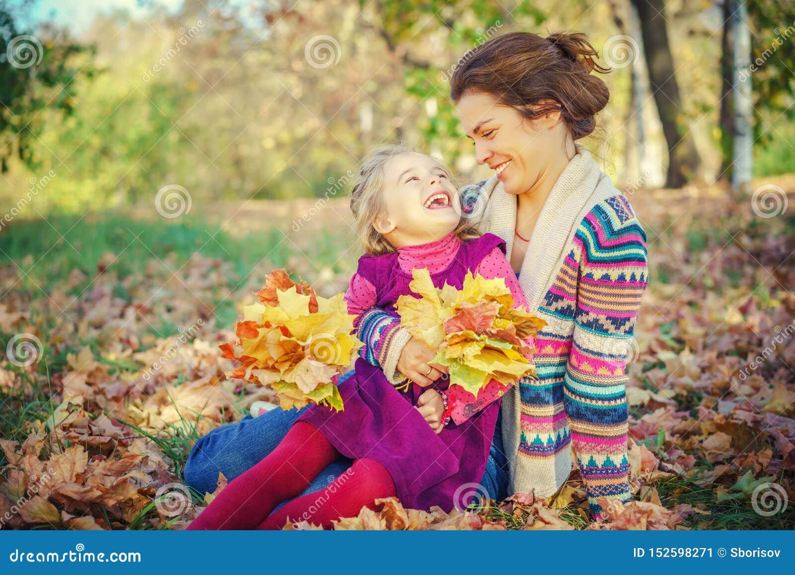 Mutter und Tochter, die im Herbstpark spielen