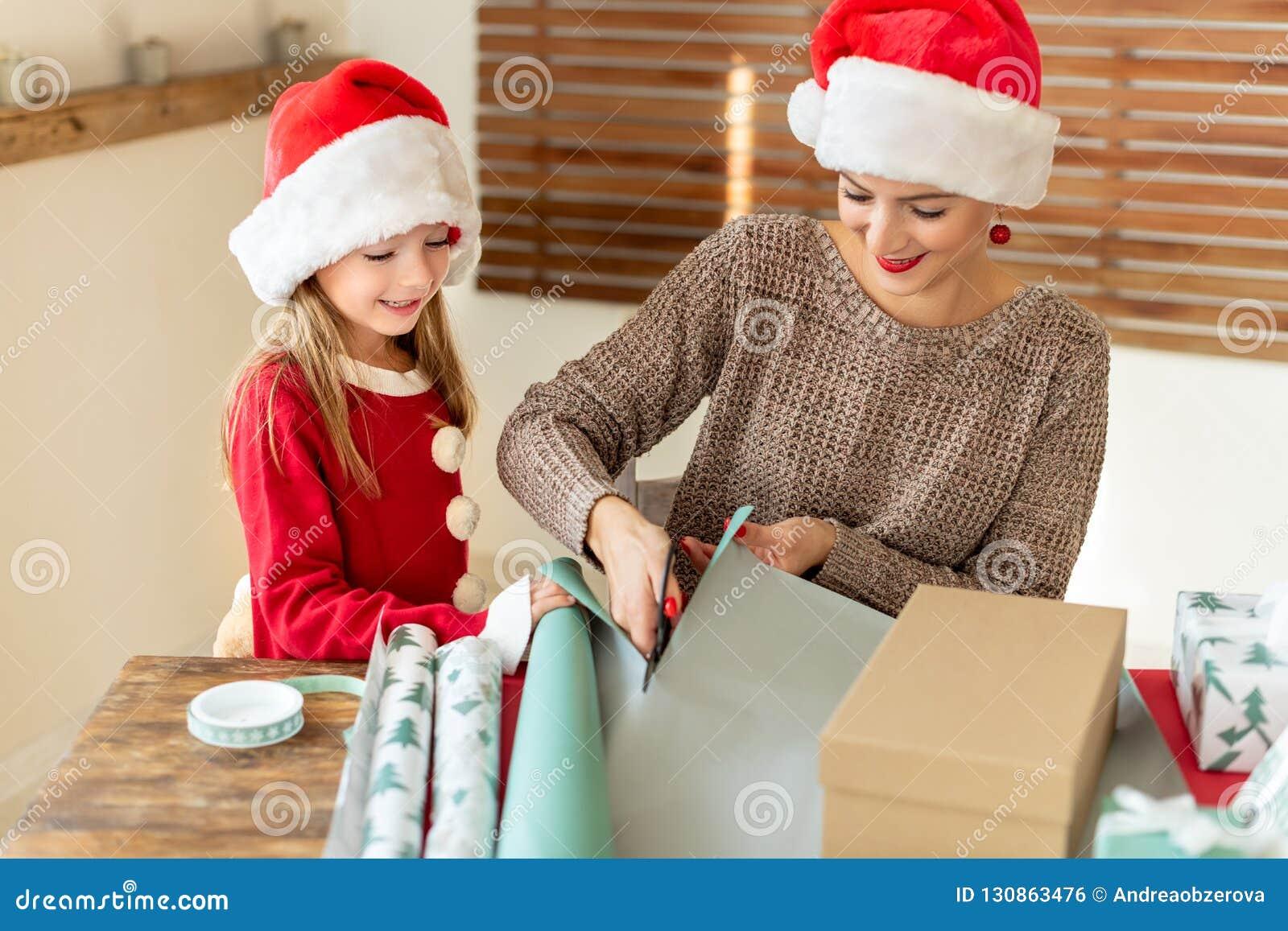 Mutter und Tochter, die Sankt-Hüte haben den Spaß zusammen einwickelt Weihnachtsgeschenke im Wohnzimmer trägt Offene Familienweih