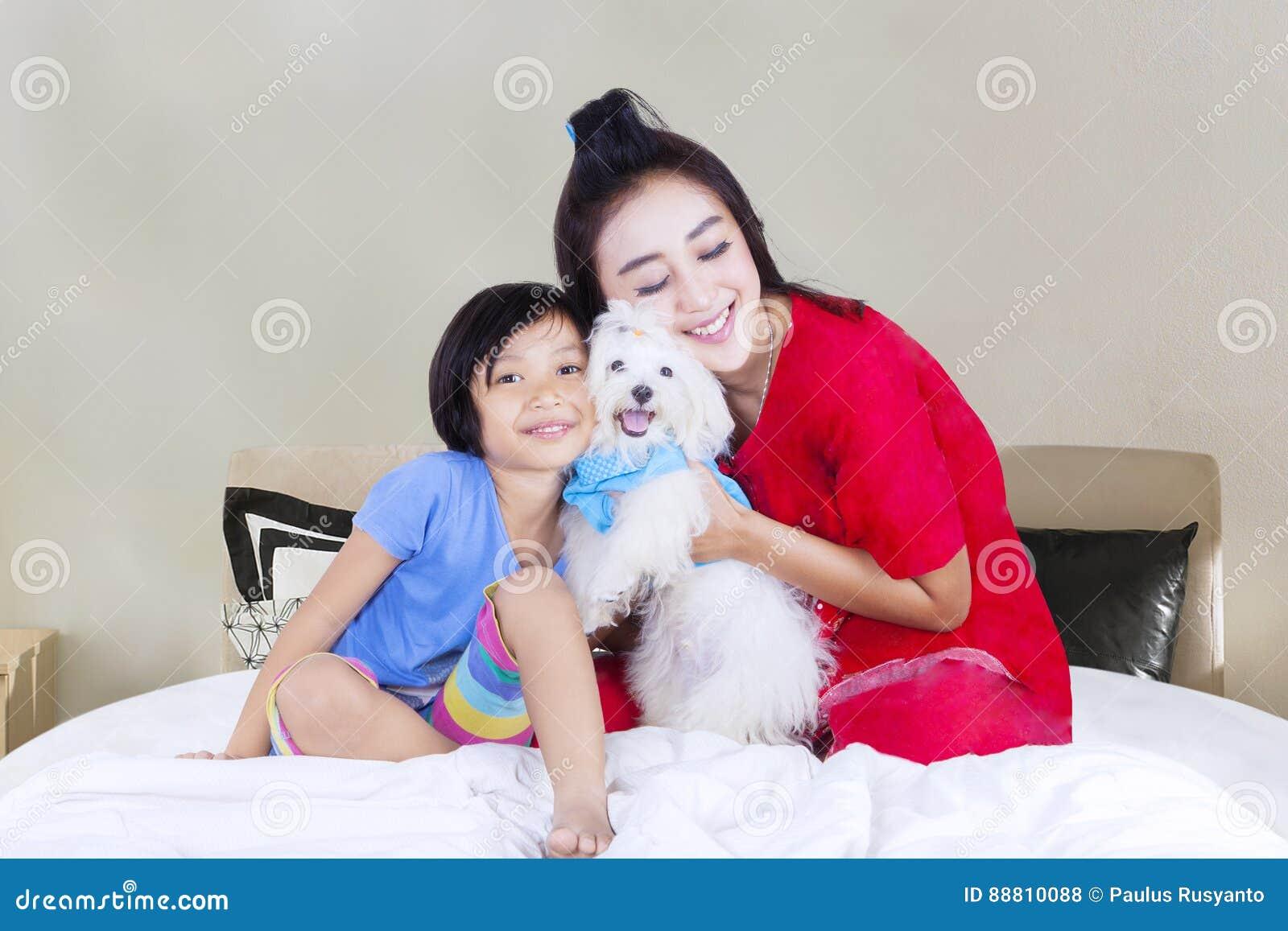 Mutter Und Tochter Mit Hund Im Schlafzimmer Stockfoto - Bild ...