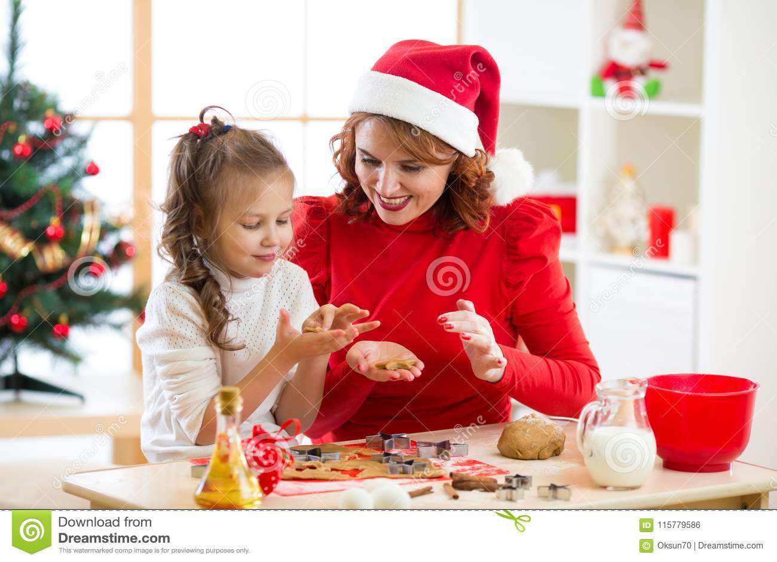 Mutter- und Tochterbacken Weihnachtsplätzchen an verziertem Baum Mutter und Kind backen Weihnachtsbonbons Familie mit Kindern
