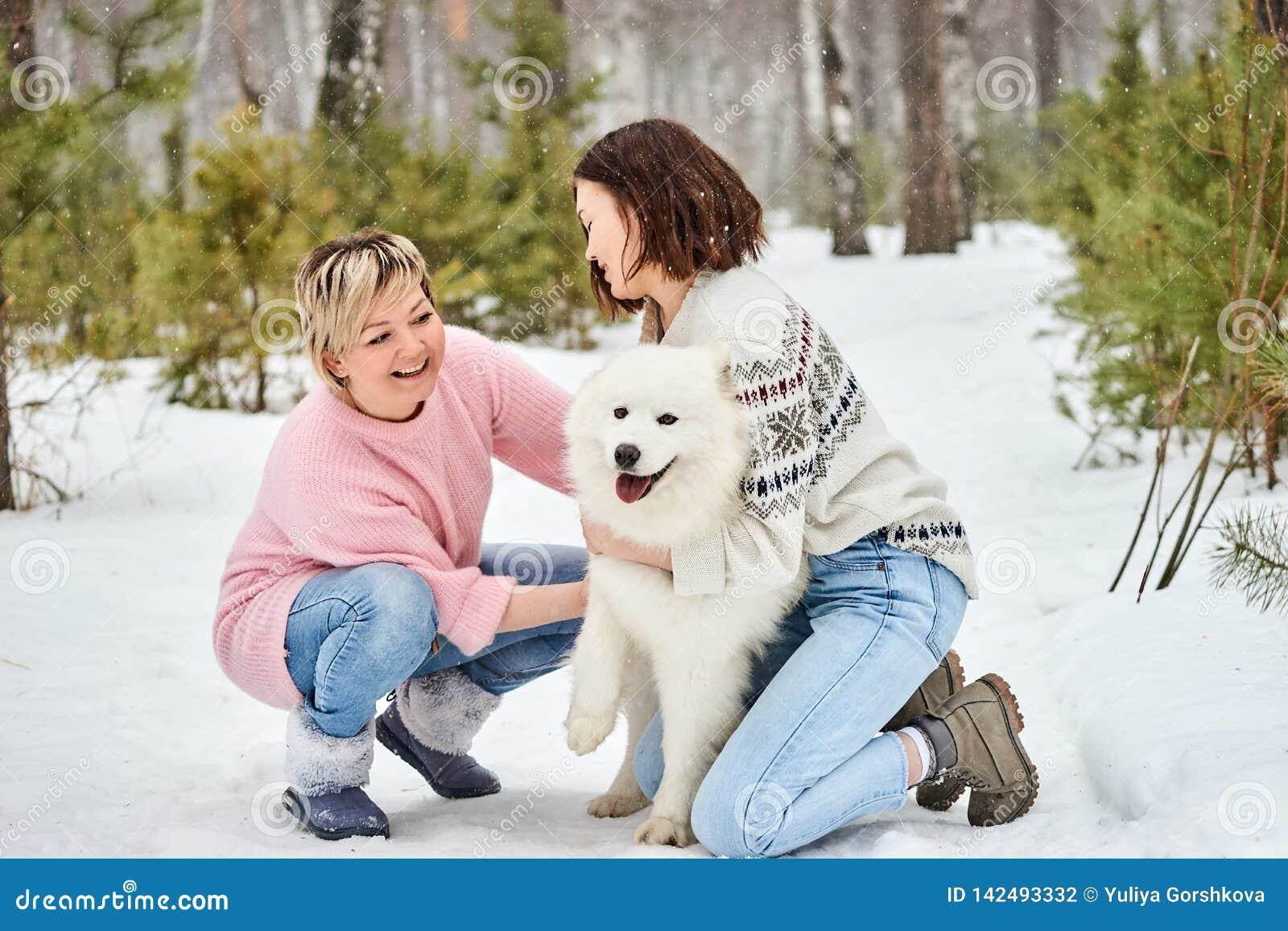 Mutter- und Tochterspiel mit Hund im Winter der Wald