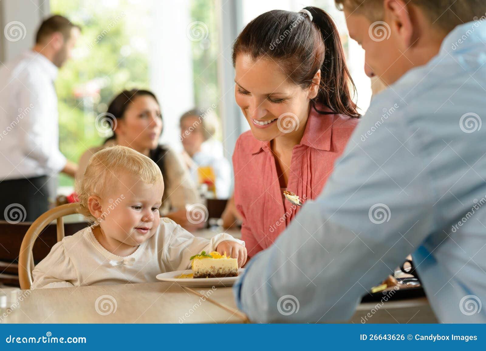 Mutter Und Vater Mit Dem Kind, Das Kuchen Isst Stockfoto