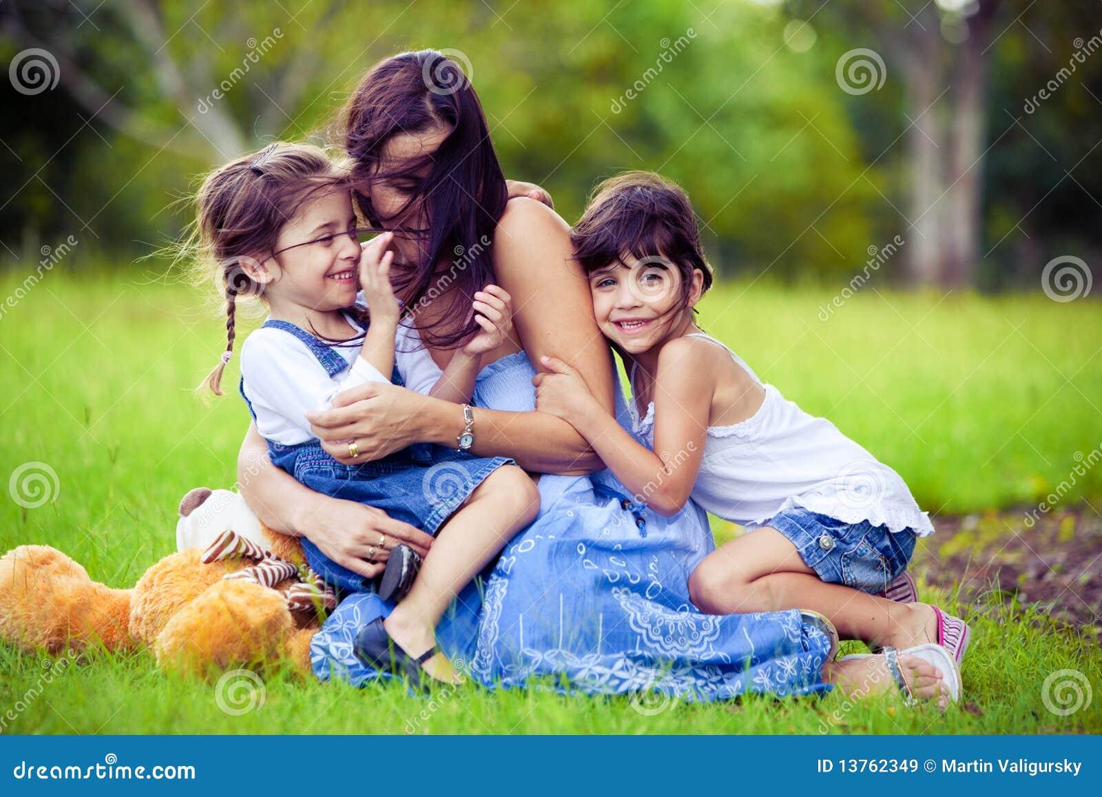 Mutter und zwei Töchter, die im Gras spielen