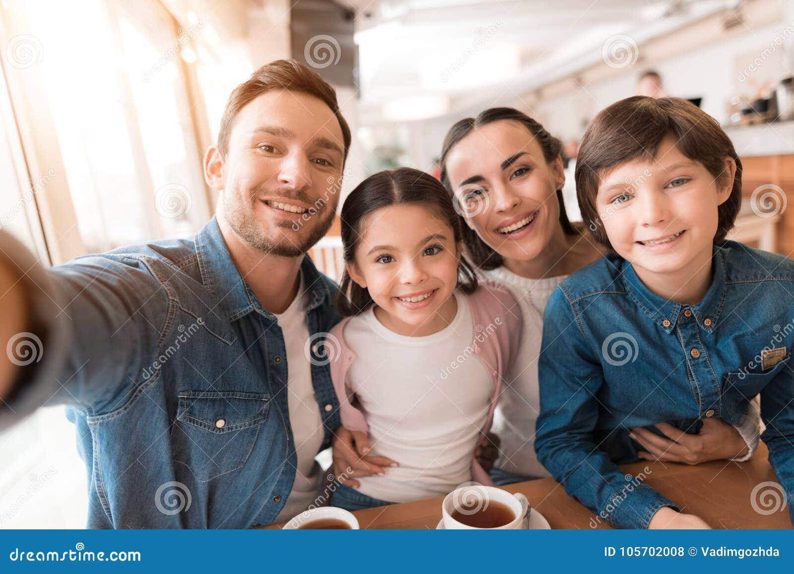 Mutter, Vati, Tochter und Sohn, die zusammen auf einer Kamera in einem Café aufwerfen