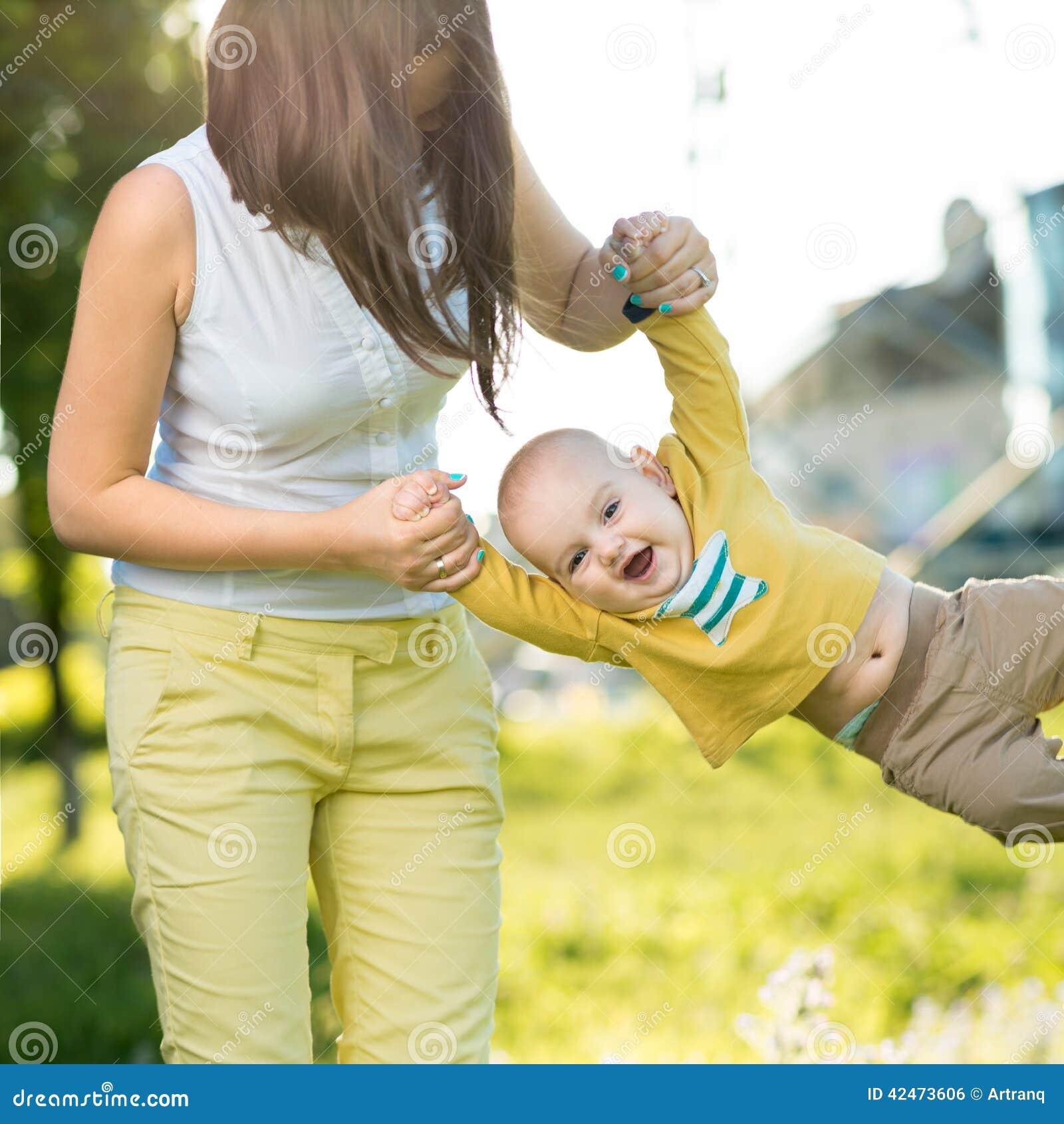 Mutter wirft Baby in ihren Armen oben