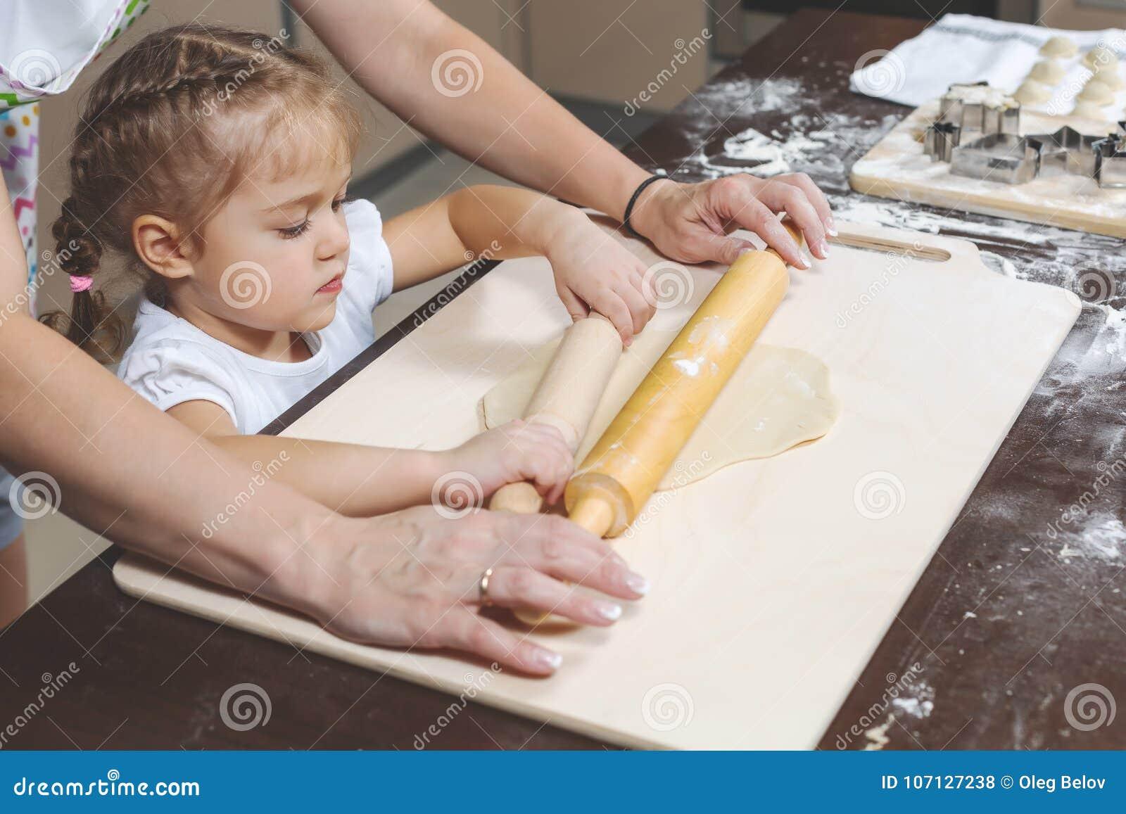 Mutter zeigt ihr Töchter, wie man Teig für die Herstellung von Mehlklößen bereitstellt