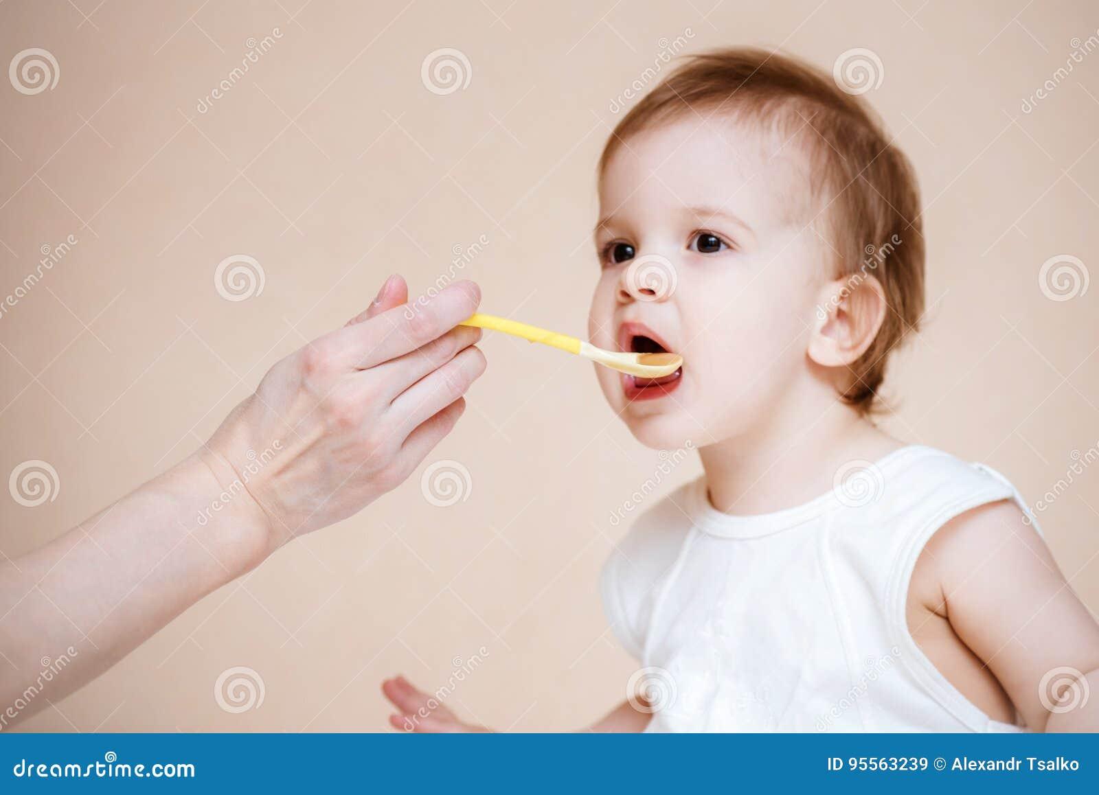 Mutter zieht das Baby mit Fruchtmus ein