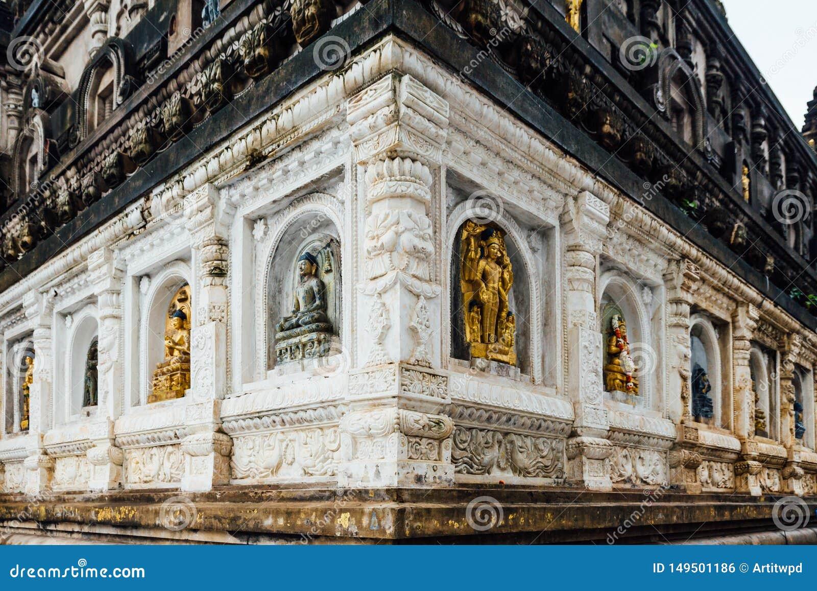 Muur van de tempel die met vele vormen en culturen van de antieke standbeelden van Boedha bij Mahabodhi-Tempel in Bodh Gaya verfr