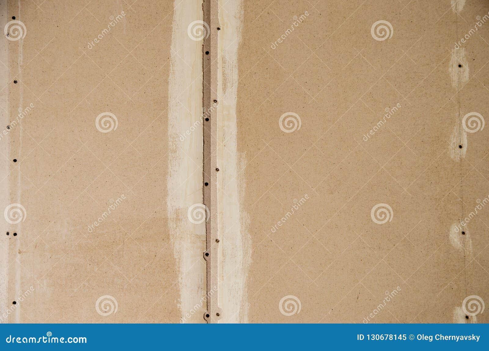 Muur van houtvezelplaat met sporen van lijm en verf
