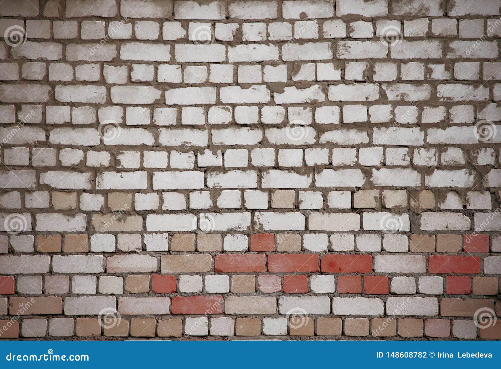 Muur van witte en rode bakstenen met ongelijk oud metselwerk