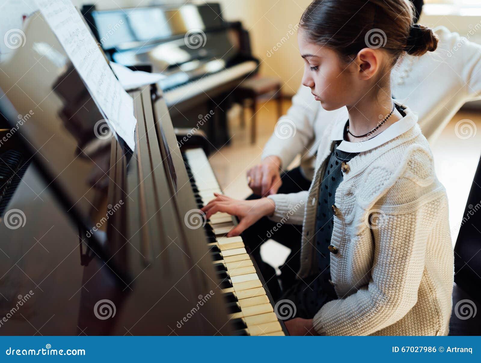 Muziekleraar met de leerling bij lessenpiano