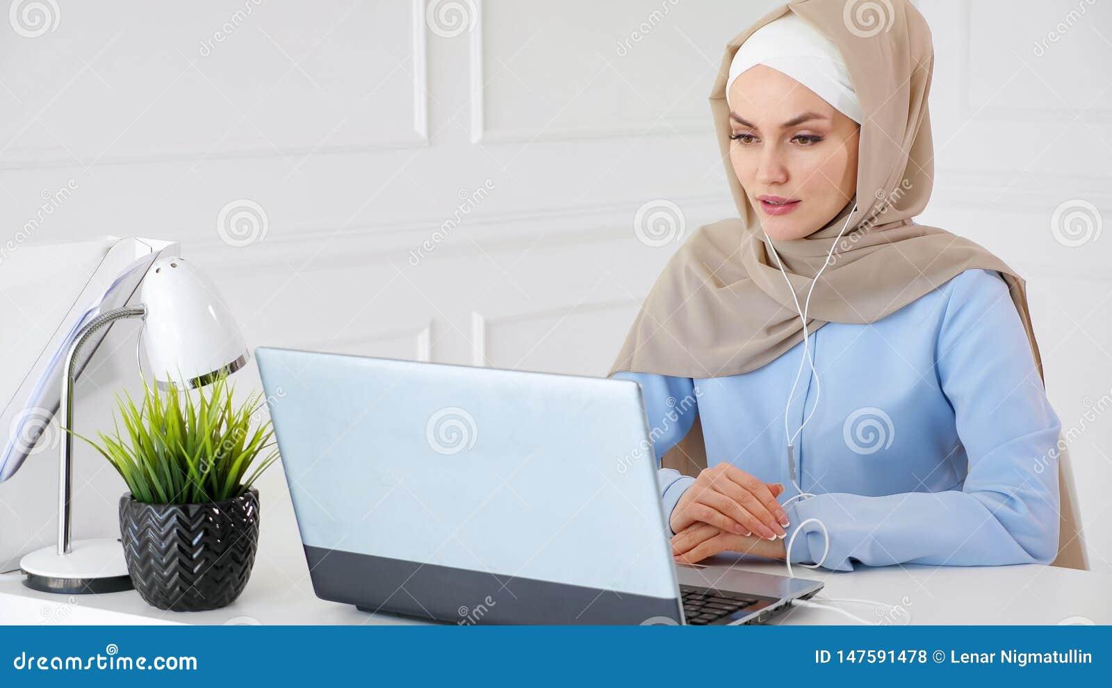 Muzu?ma?ska kobieta uczy si? anglik?w w s?uchawka online u?ywa komputerze