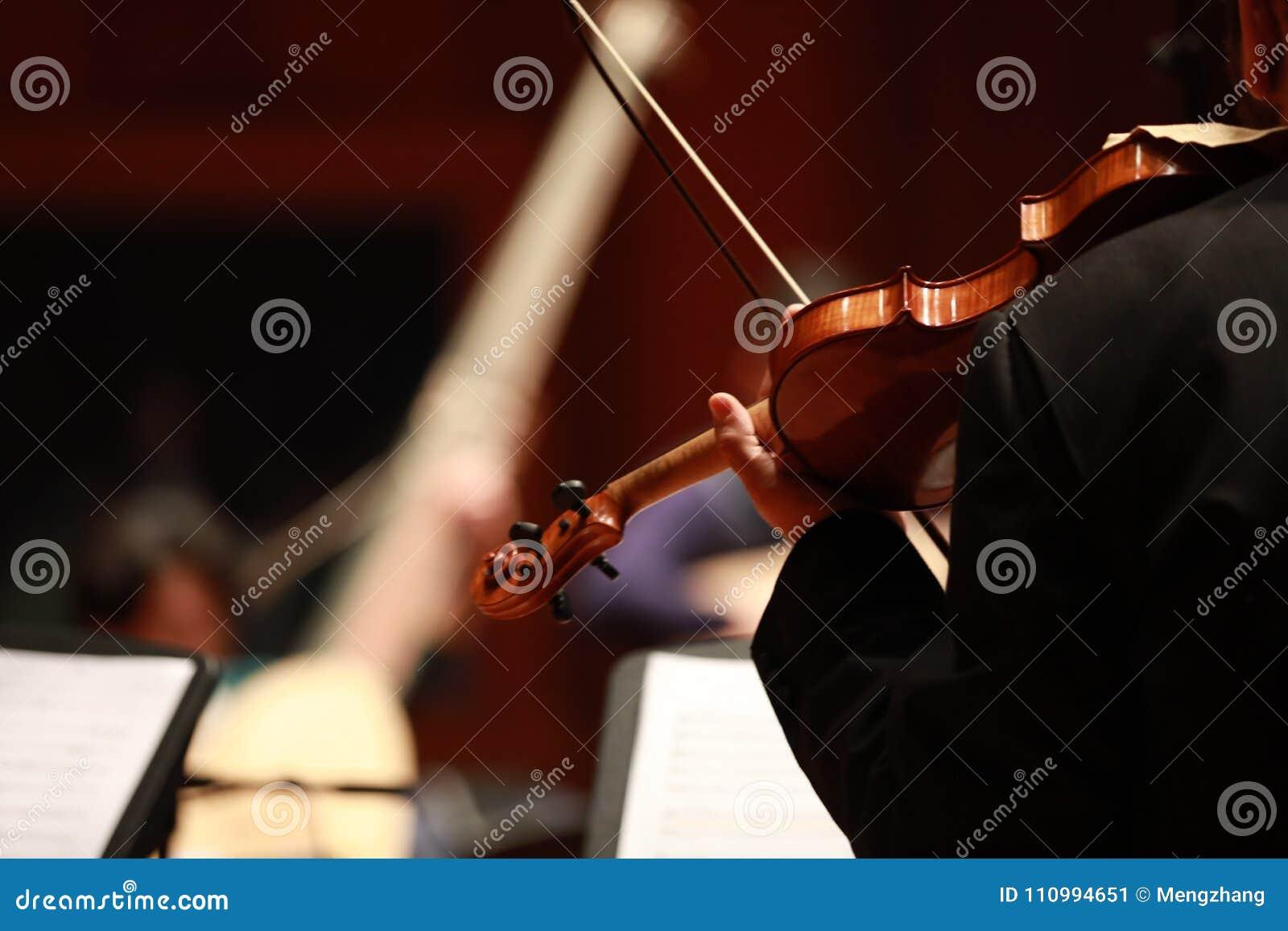 Muzyka klasyczna Skrzypaczki w koncercie Nawleczony, violinistCloseup bawić się skrzypce podczas symfoni muzyk