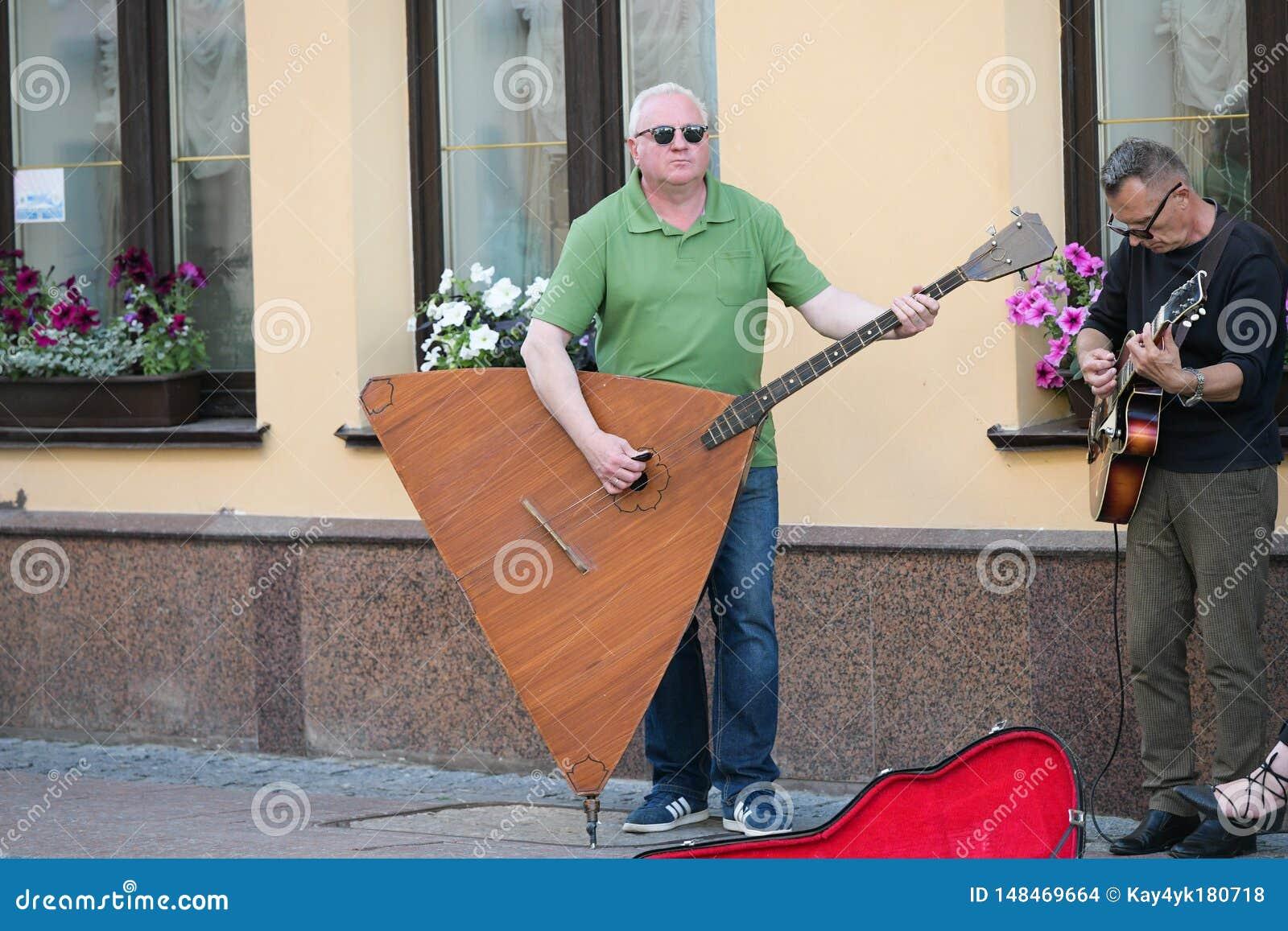 Muzykalna grupa trzy ludzie na starej Europejskiej ulicie Zesp?? sk?ada? si? z dwa m??czyzna i jeden dziewczyna M??czyzna z dwois