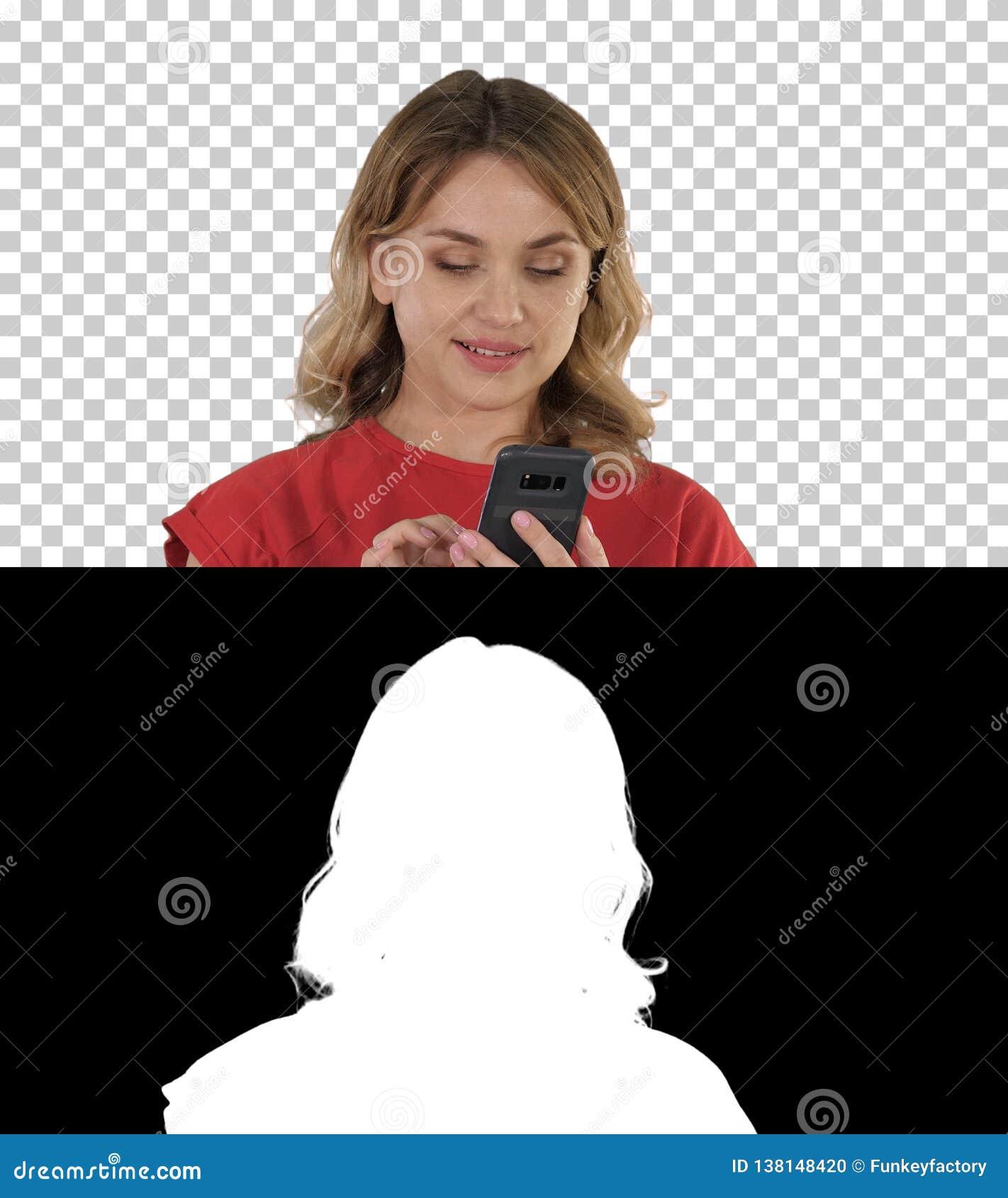 Myśląca ładna blondynka wysyła tekst na jej telefonie, Alfa kanał