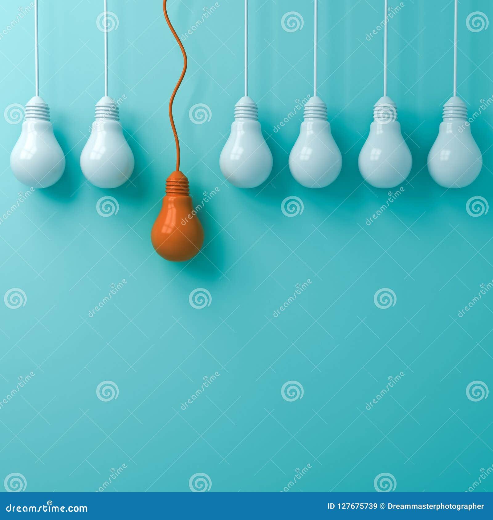 Myśleć różny Jeden pojęcia wiszącą pomarańczową żarówkę stoi out od ciemnawych światło białe żarówek na zielonym pastelowym kolor
