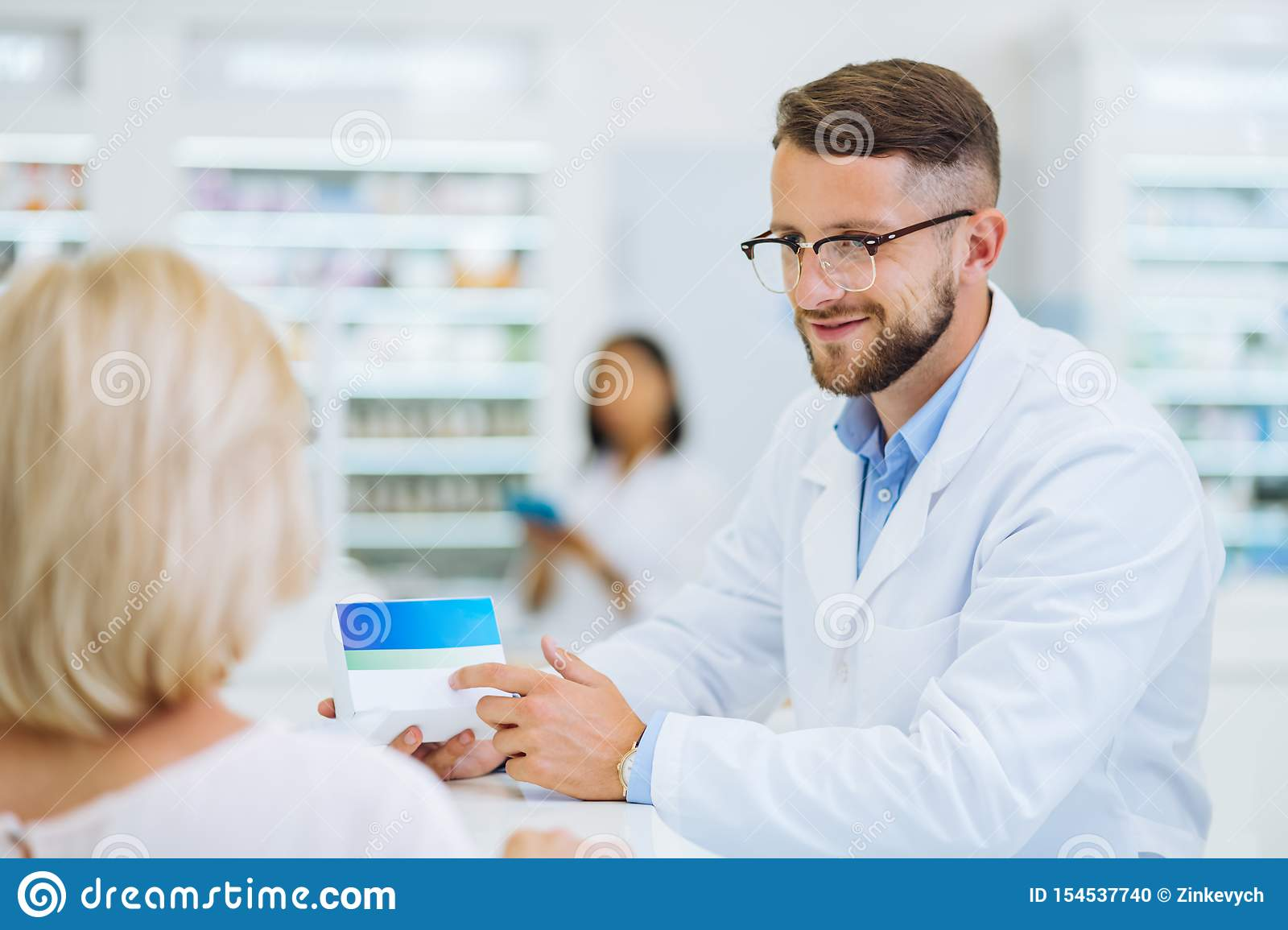 Cheerful young male person pointing at pills