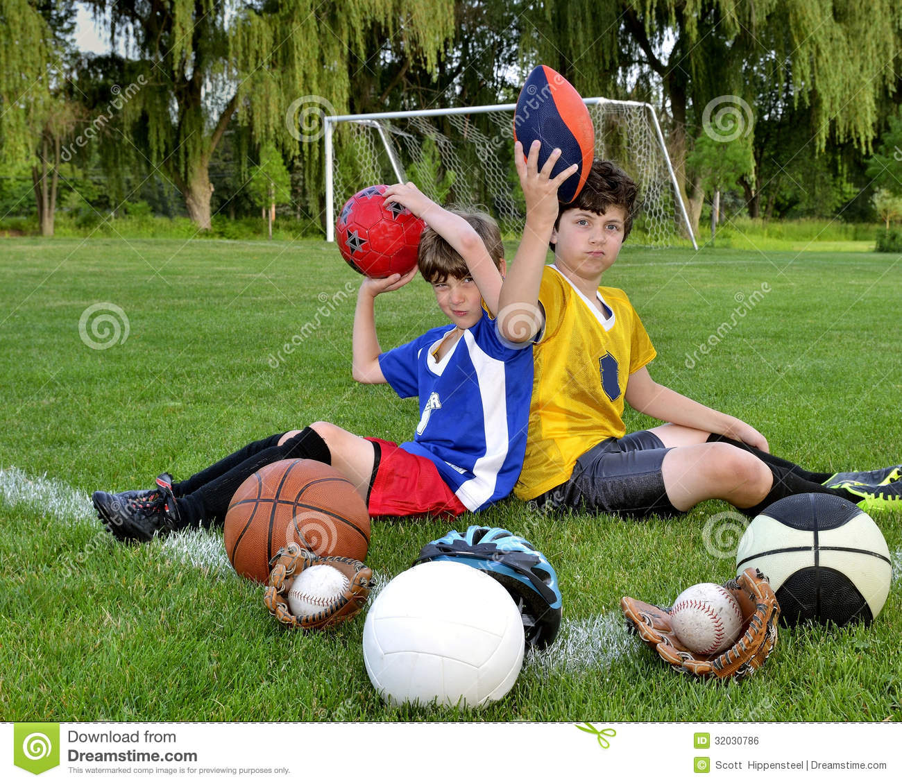 Two boys sitting on a soccer field surrounded by various sports ...