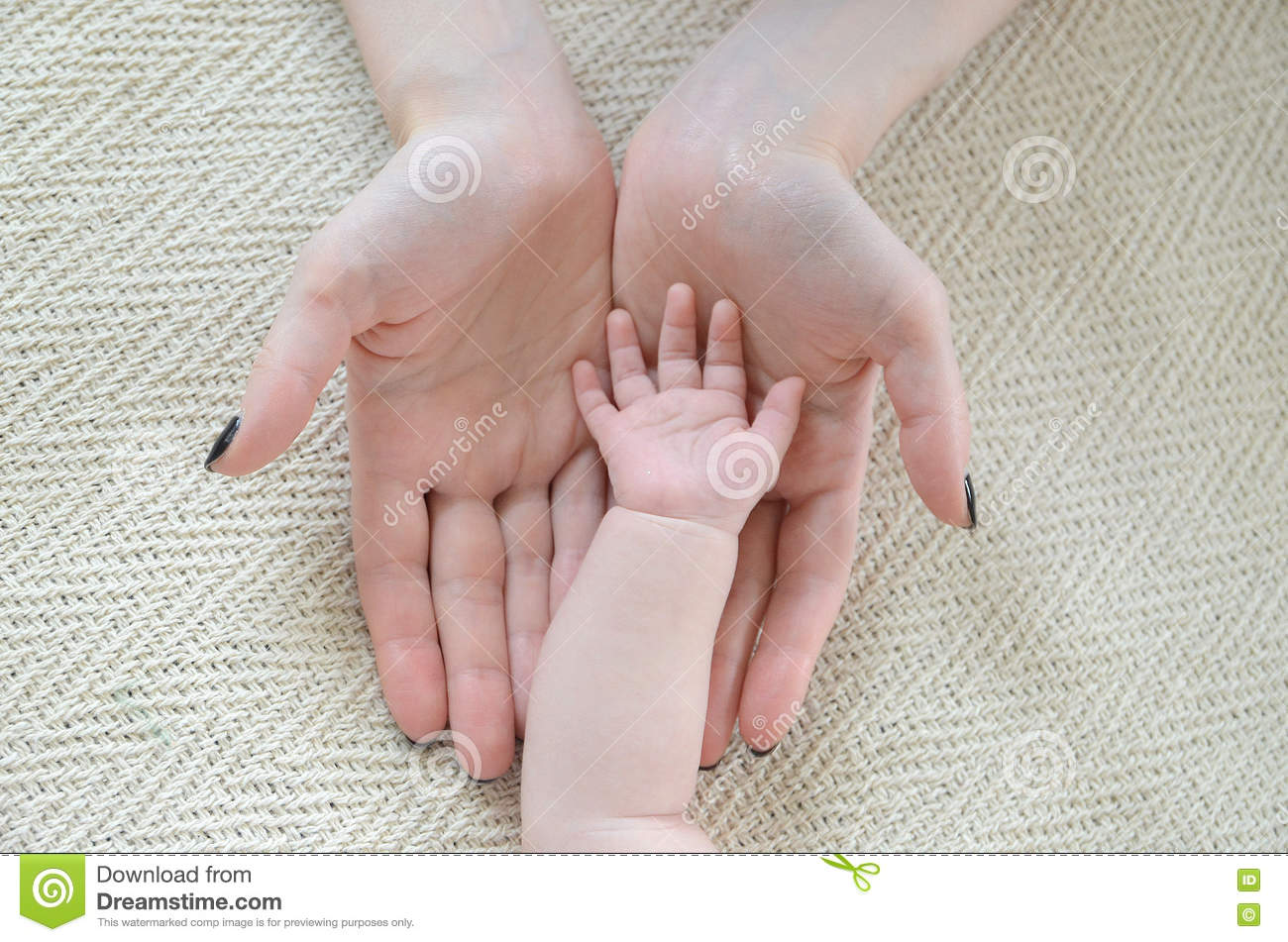 Little child's hand in mother's arms