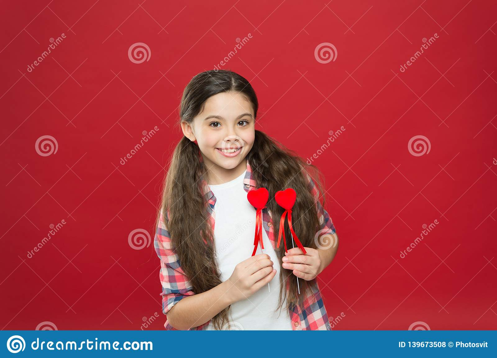 My love for you is forever. Small girl holding hearts on sticks. Cute girl with small red hearts. Small child with heart