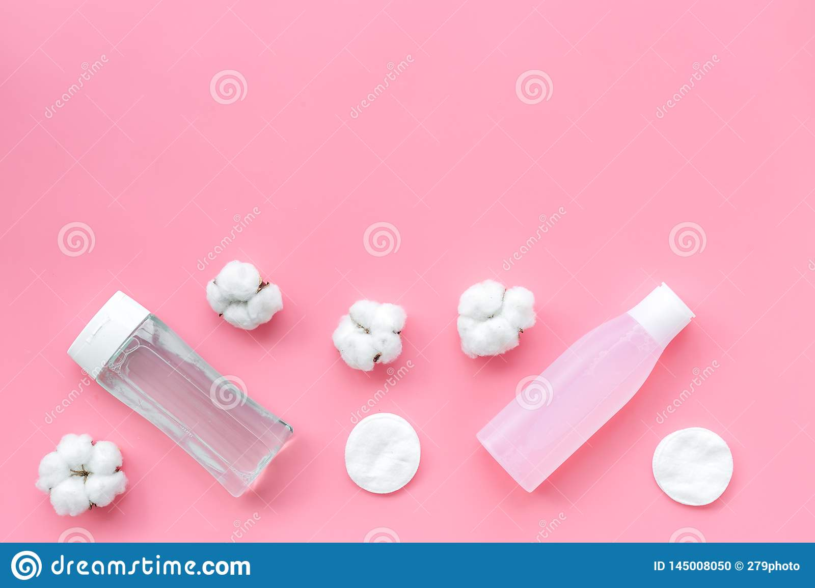 Mycelial water, lotion and cotton pads for skin care on pink background flat lay space for text