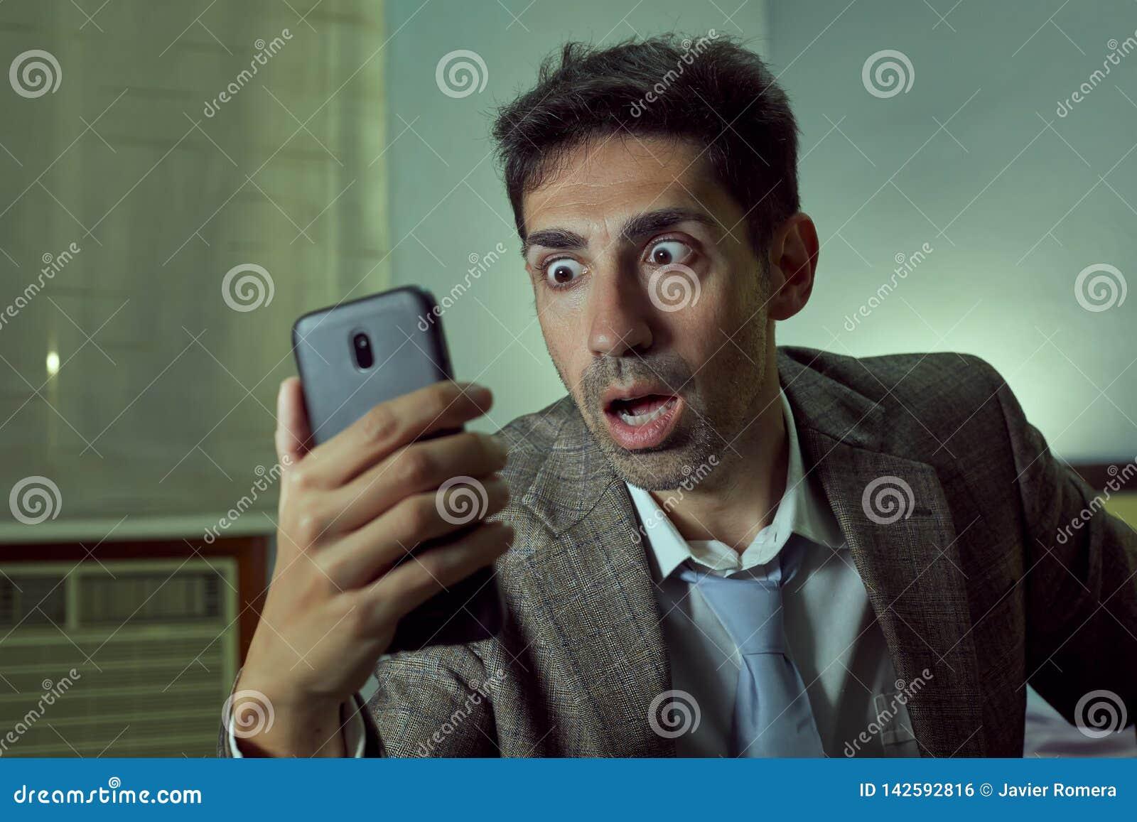 Mycket förvånad man som ser hans smartphone i ett rum