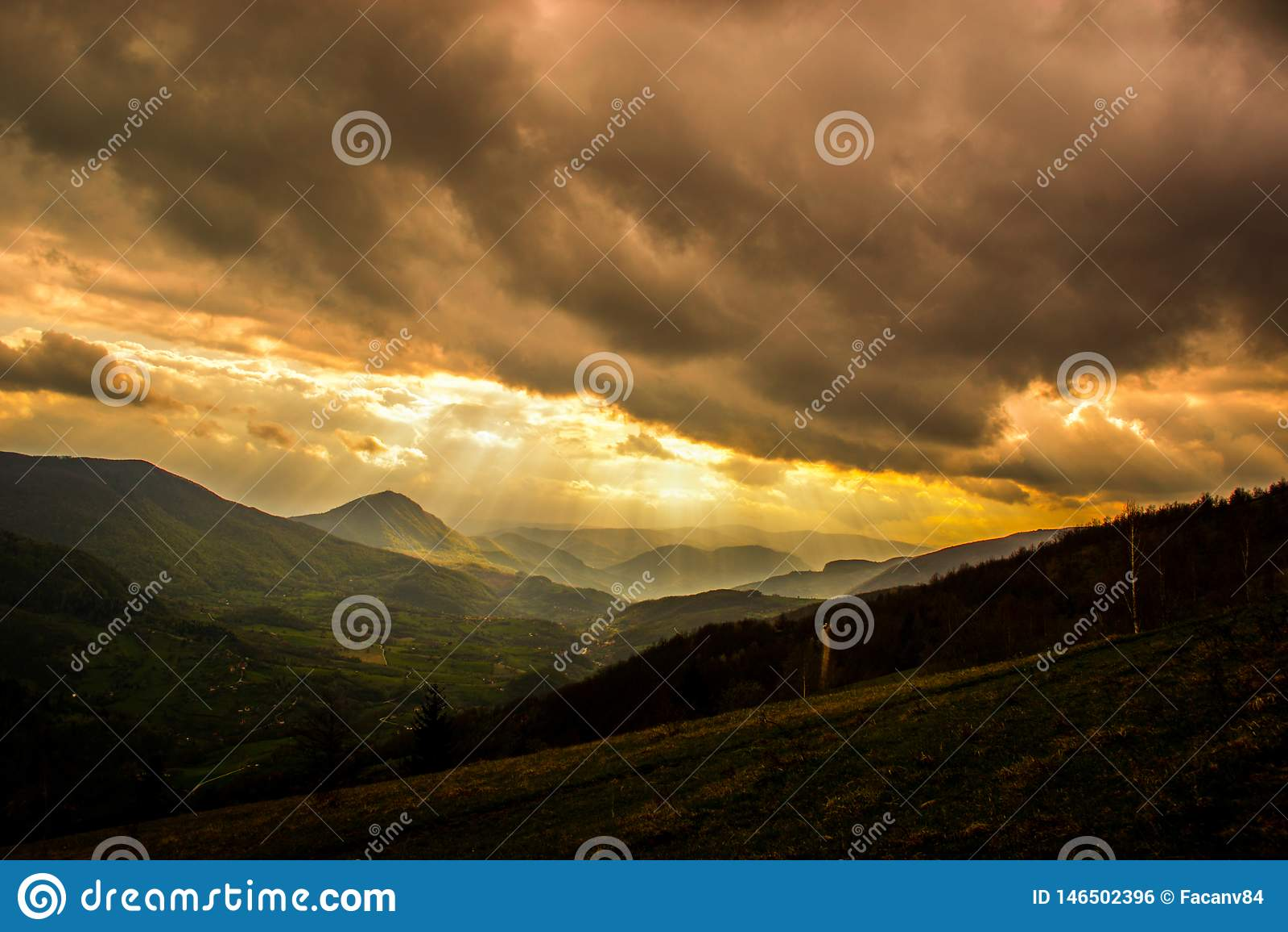Mycket intressant solnedg?ng Sikt av v?rlandskap, solljus och m?rka moln ?ver
