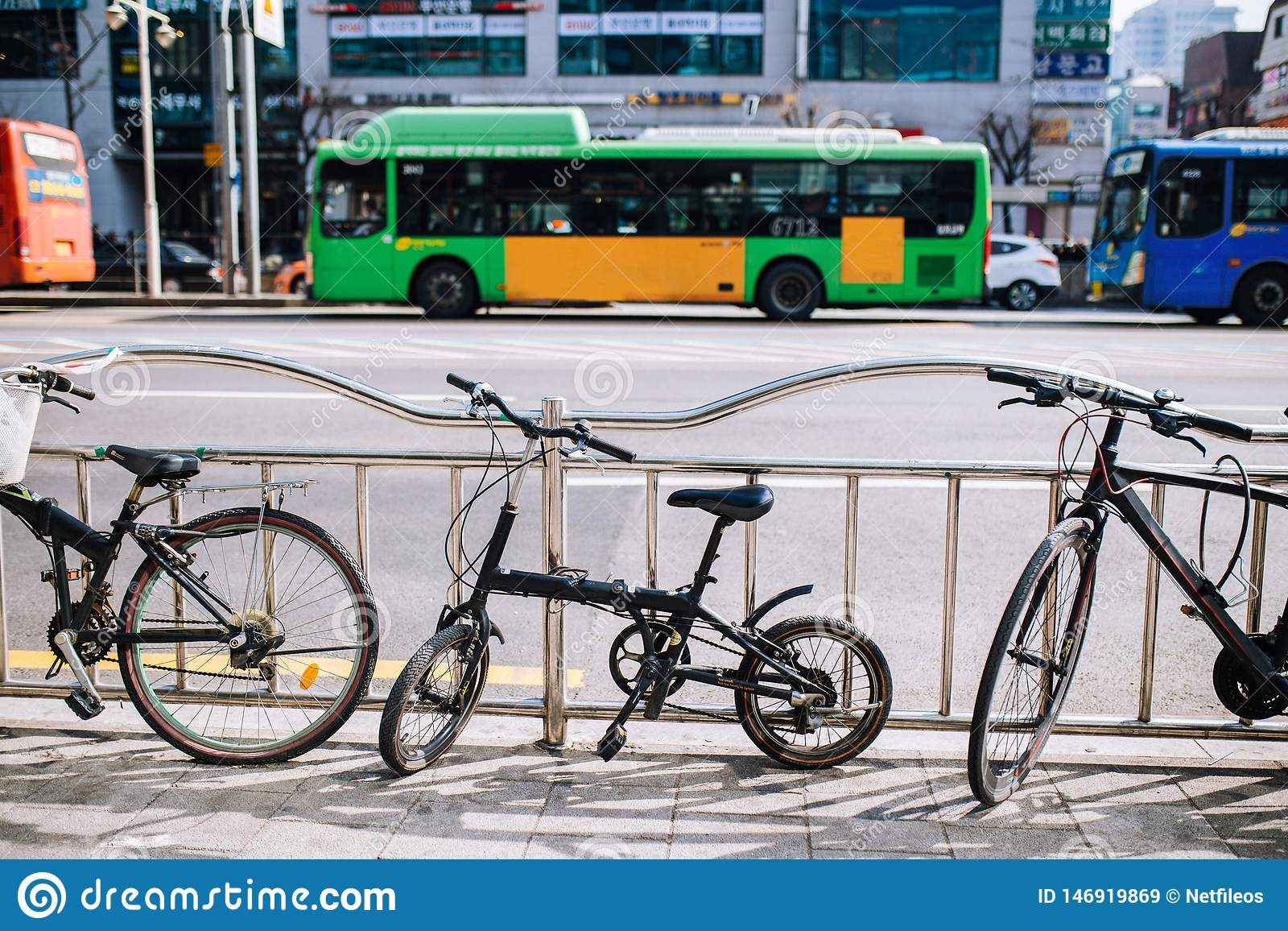 Mycket liten hopfällbar cykel på stadsgatan parkera på staketsideroad, den stads- platsen, cykeln och bussen
