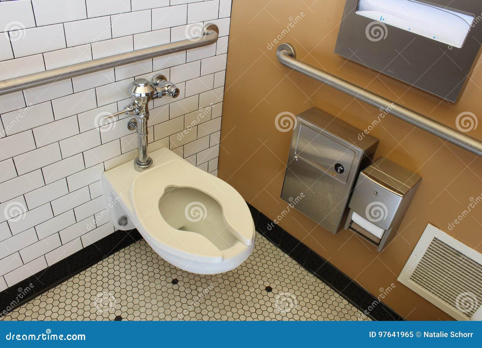 Mycket ren offentlig damtoalett med den belade med tegel väggen och golvet