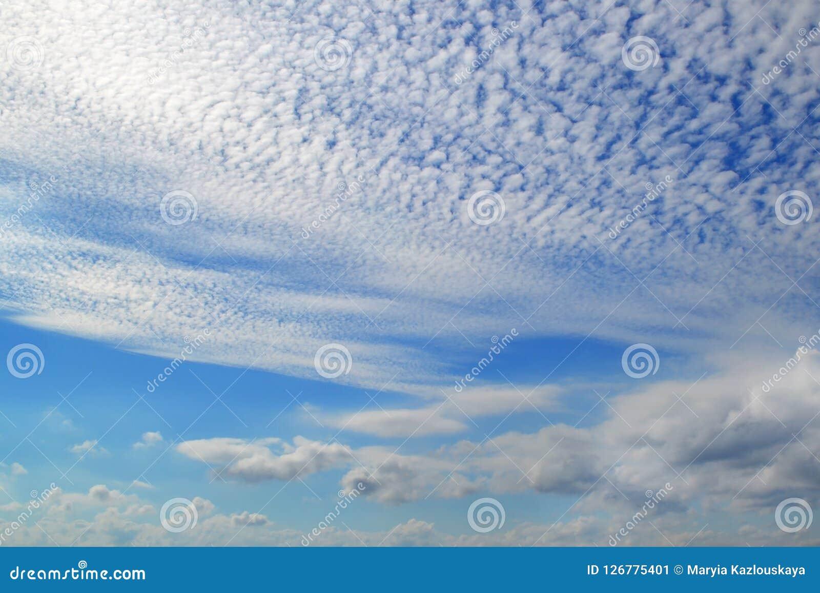 Mycket vita moln av olika typer: stackmoln cirrusmoln, i lager höjdpunkt i blå himmel