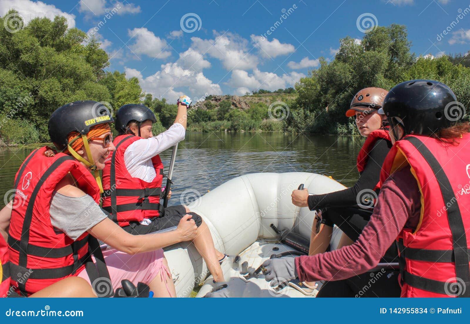 Mygiya/Ucrania - 22 de julio de 2018: POV El equipo de mujeres en transportar en balsa El transportar en balsa en el río meridion
